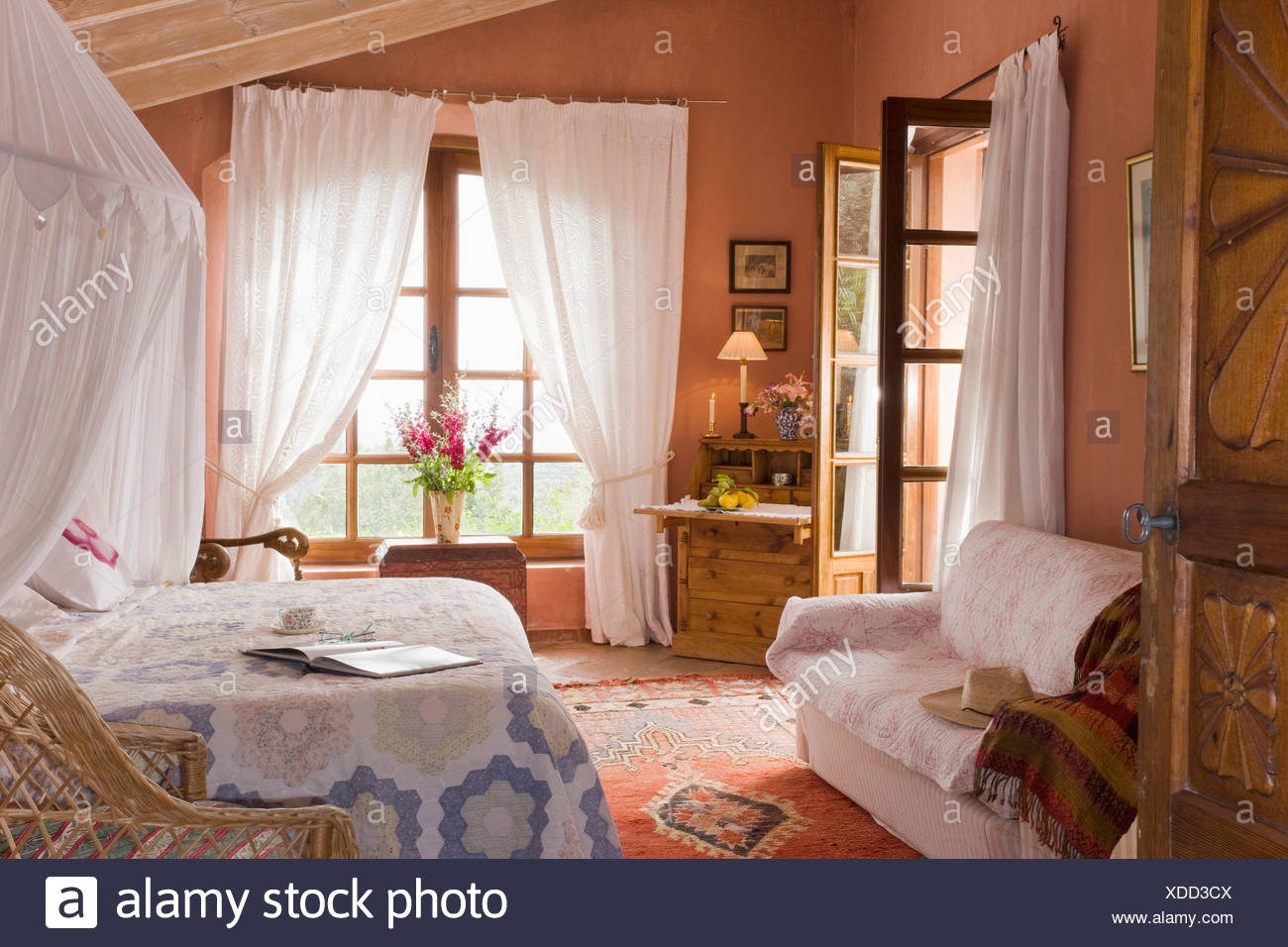 White Mosquito Net Above Bed With Patchwork Quilt In Terracotta