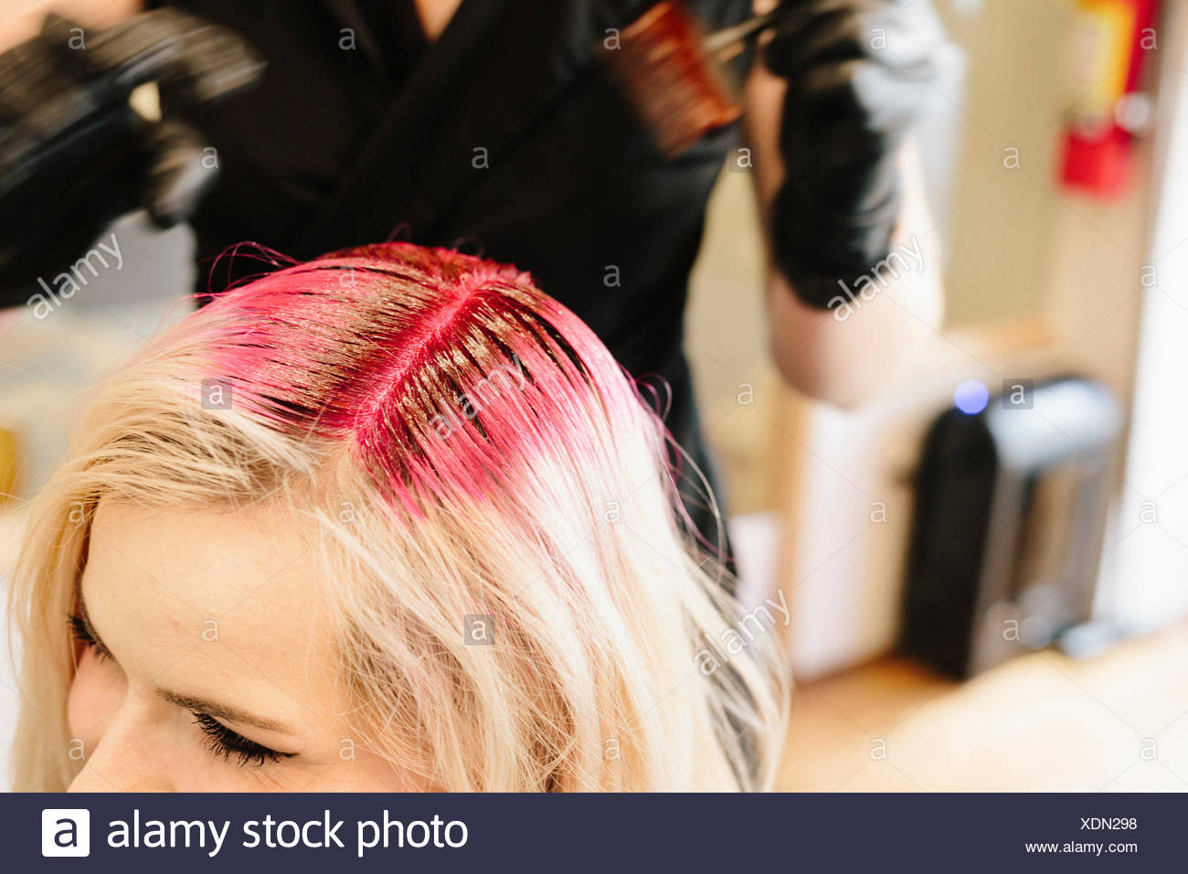 A Hair Colourist In Gloves Applying Red Hair Dye To A Clients