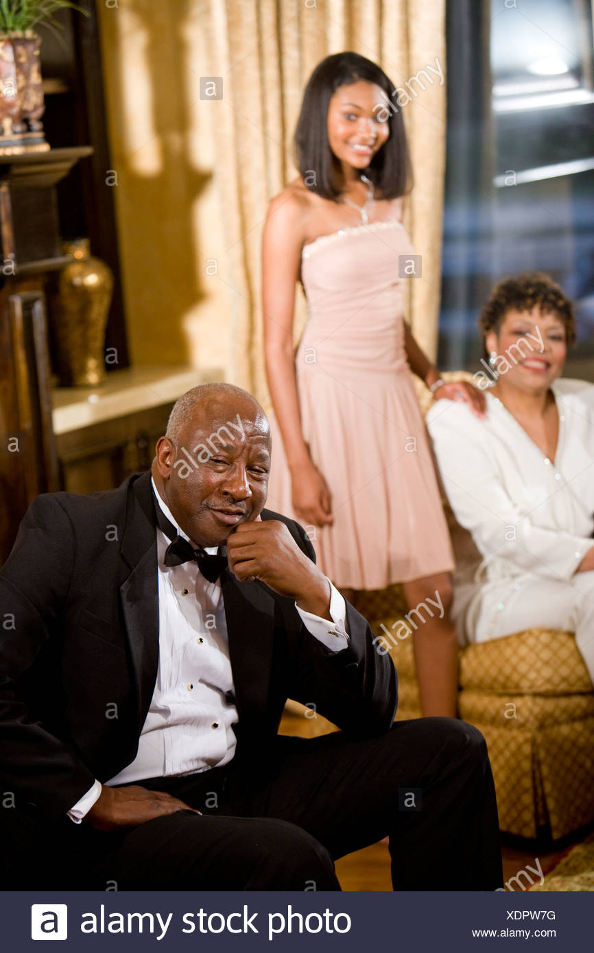6a894ba6439 Teenage girl posing with grandparents in formal attire at home Stock ...