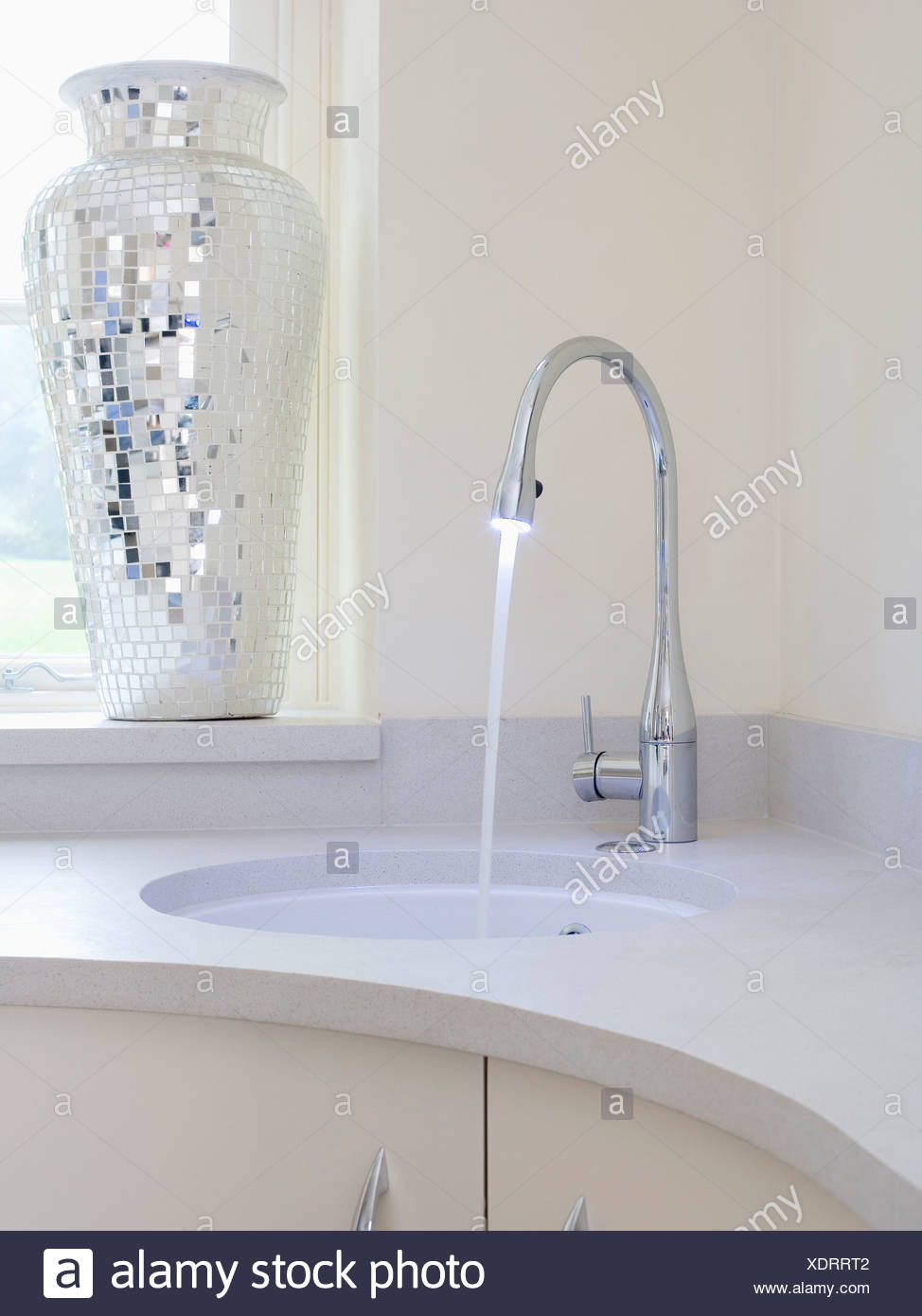 Close-up of mixer tap pouring water into under-set bathroom basin in ...