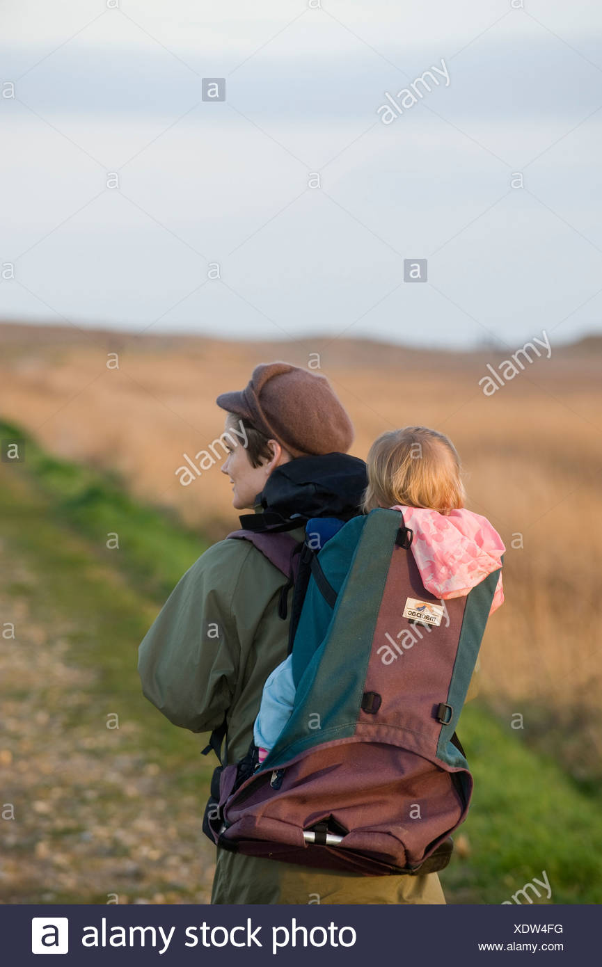 79872395f2 mother carrying toddler in backpack along coastal path North Norfolk winter