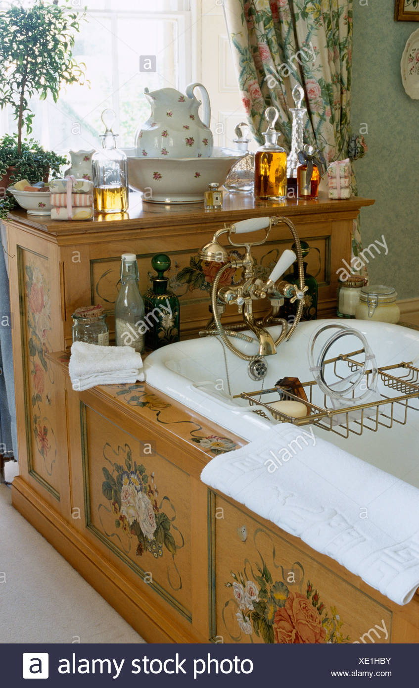Brass bath rack and taps on roll top bath set in wooden surround ...