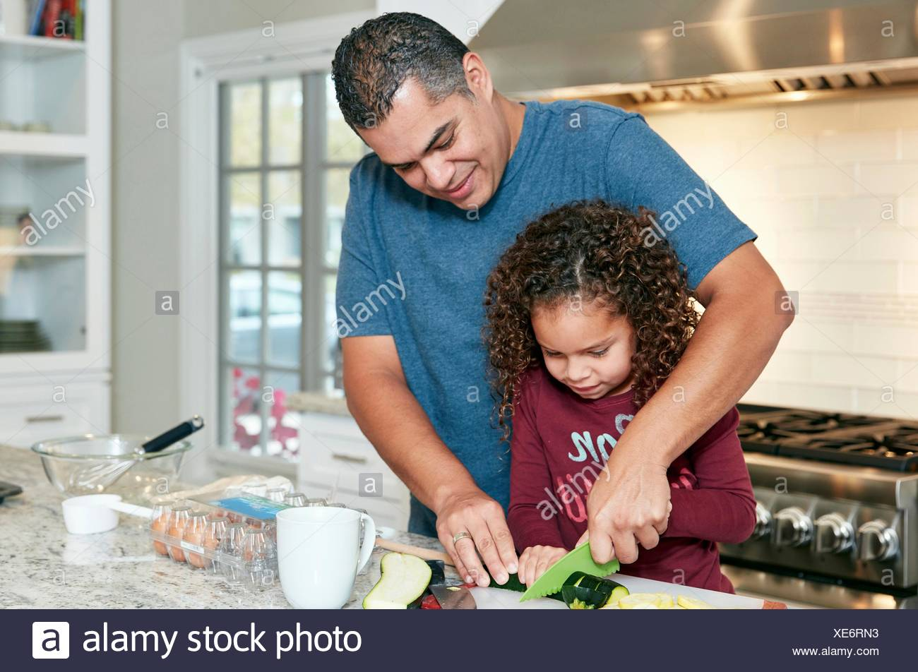 Father helping daughter chop vegetables in kitchen Stock Photo ...
