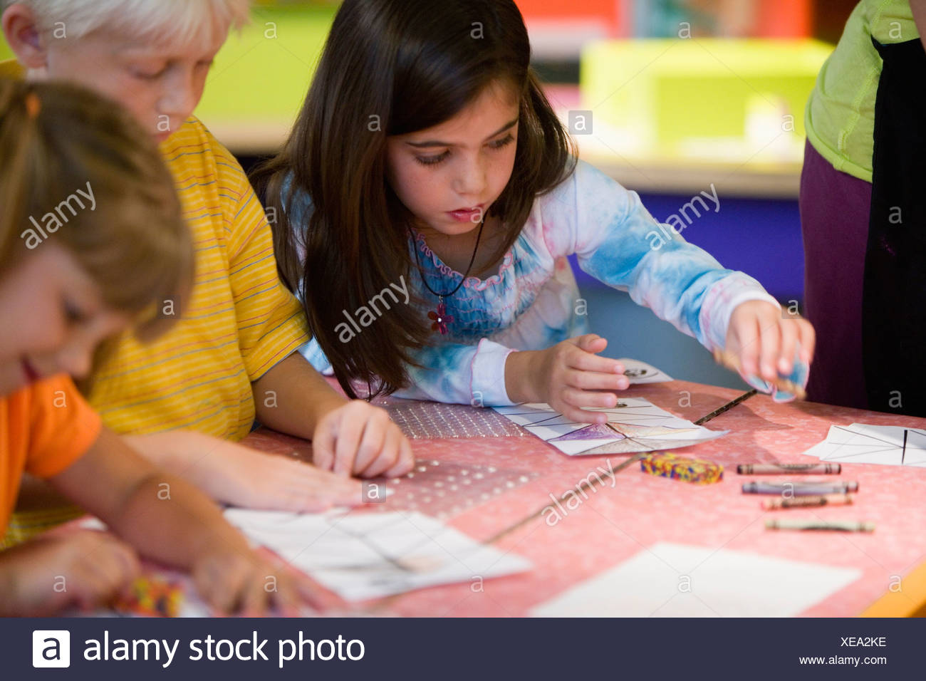 Three Children Coloring With Crayons