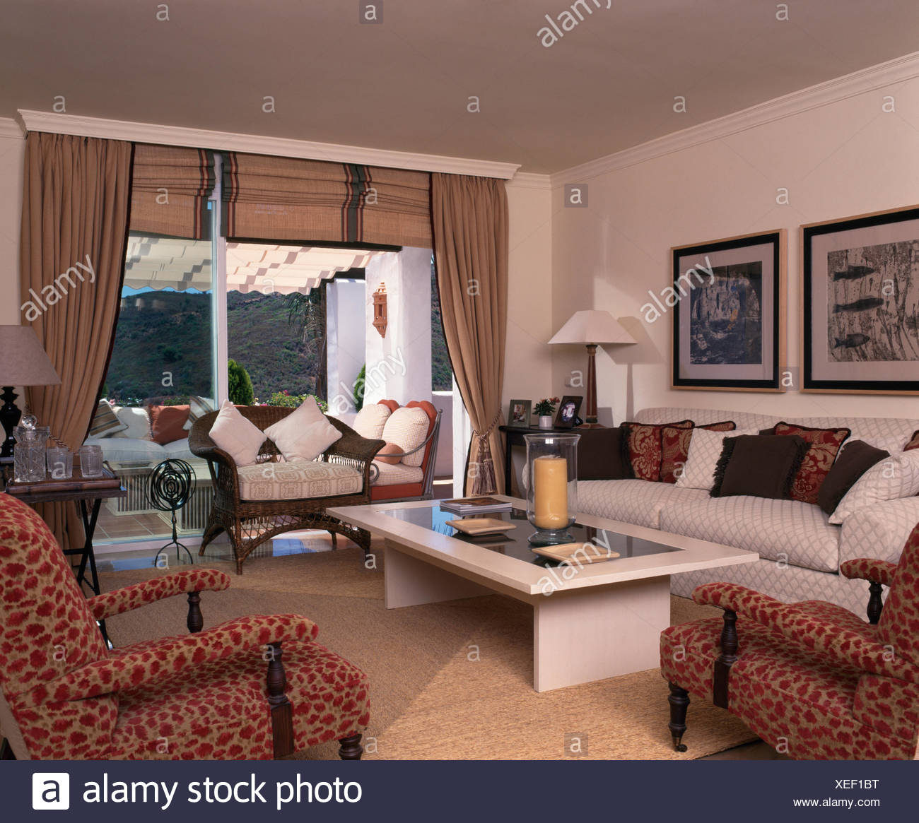 drapes and blinds floor to ceiling patterned armchairs and white coffee table in modern spanish living room with beige linen drapes blinds