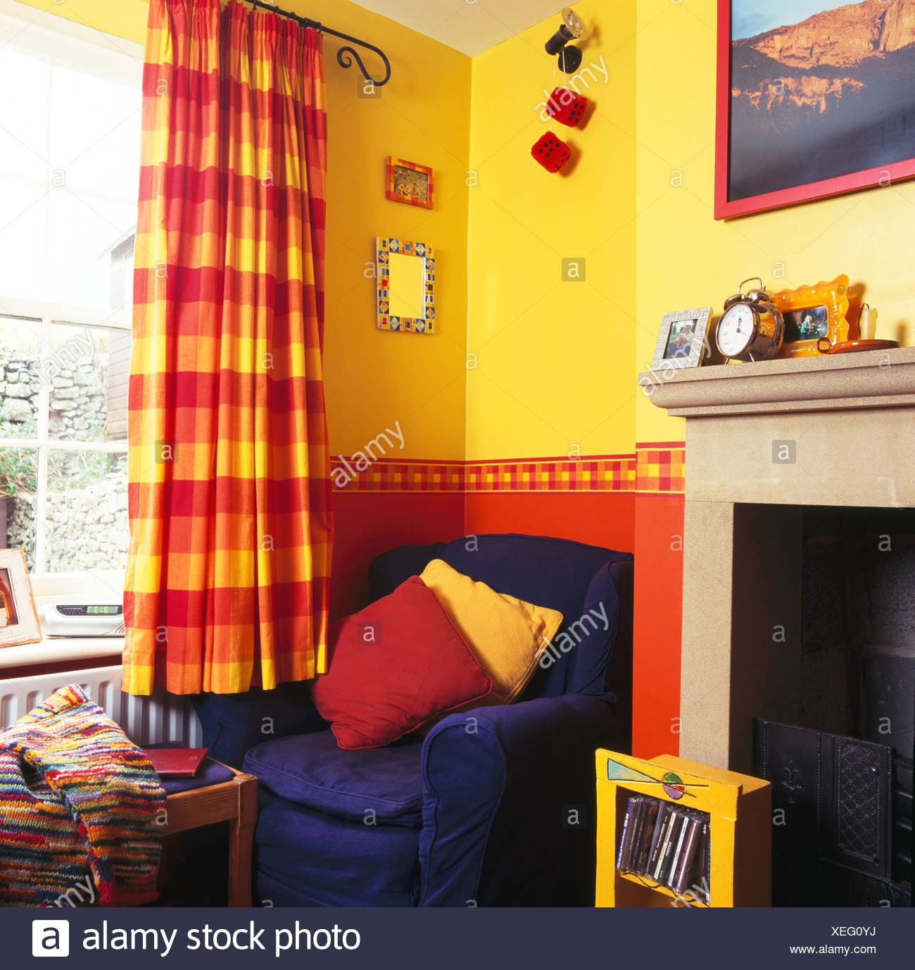 Blue Armchair In Corner Of Bright Yellow Living Room With Red+yellow  Checked Curtains And Painted Red Dado
