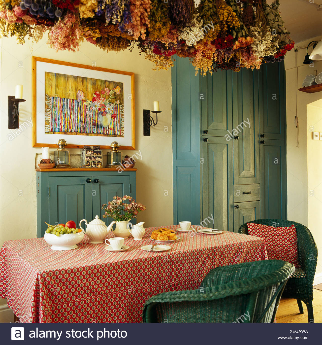 Dried Flowers On Ceiling Above Table With Pink Cloth In Traditional Dining  Room With Picture On Wall Above Painted Blue Cupboard