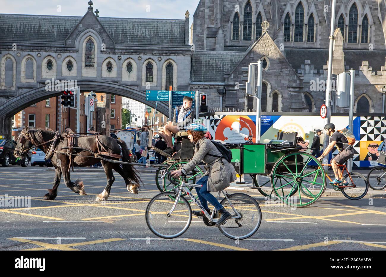 Ein Mann auf einem Fahrrad und einer Pferdekutsche Anteil der Straße in Dublin, Irland. Stockfoto