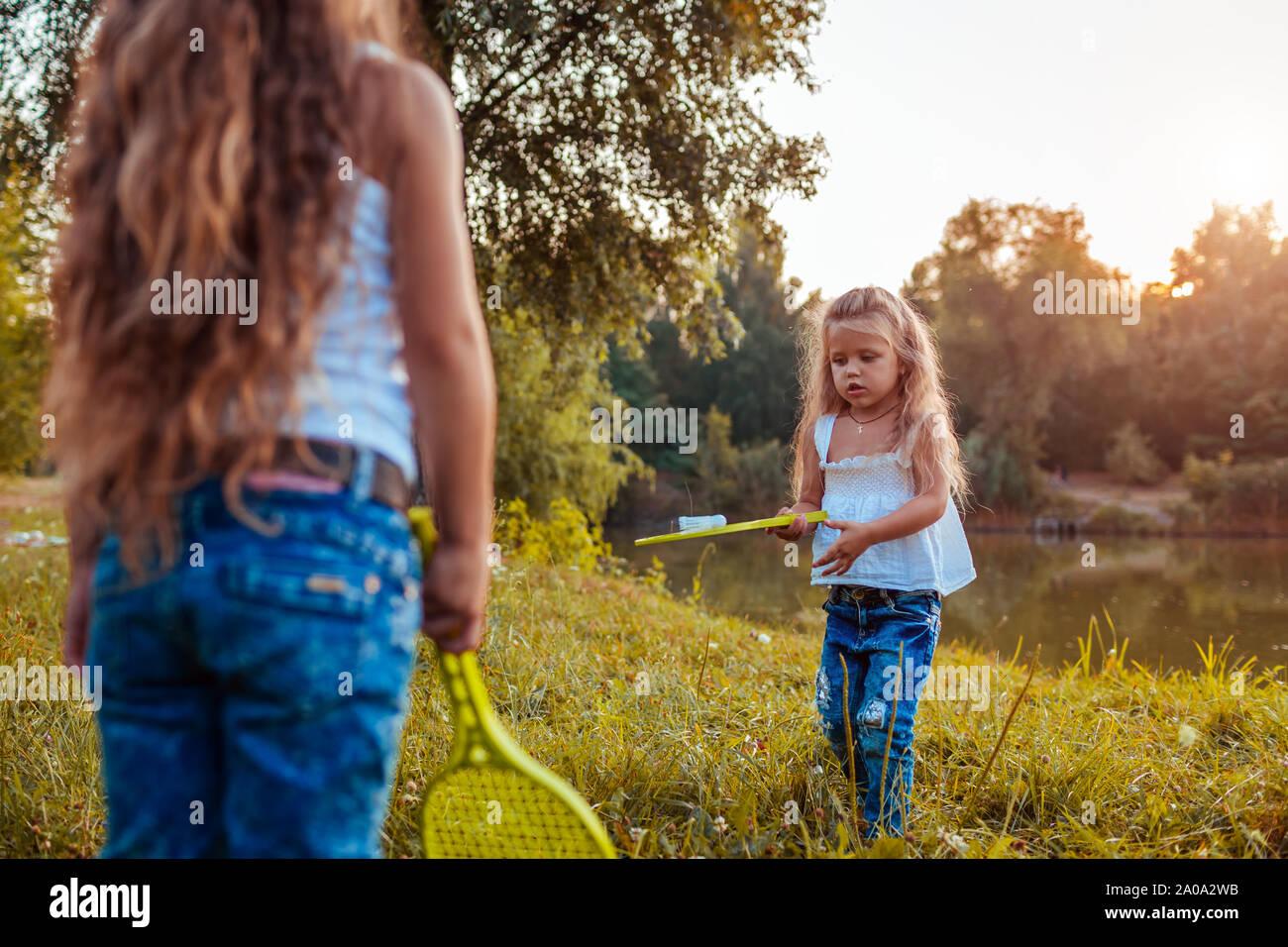 Badminton. Kleine Mädchen spielen Badminton mit Schwester im Sommer Park. Kinder Spaß im Freien. Spiele im Freien für Kinder Stockfoto