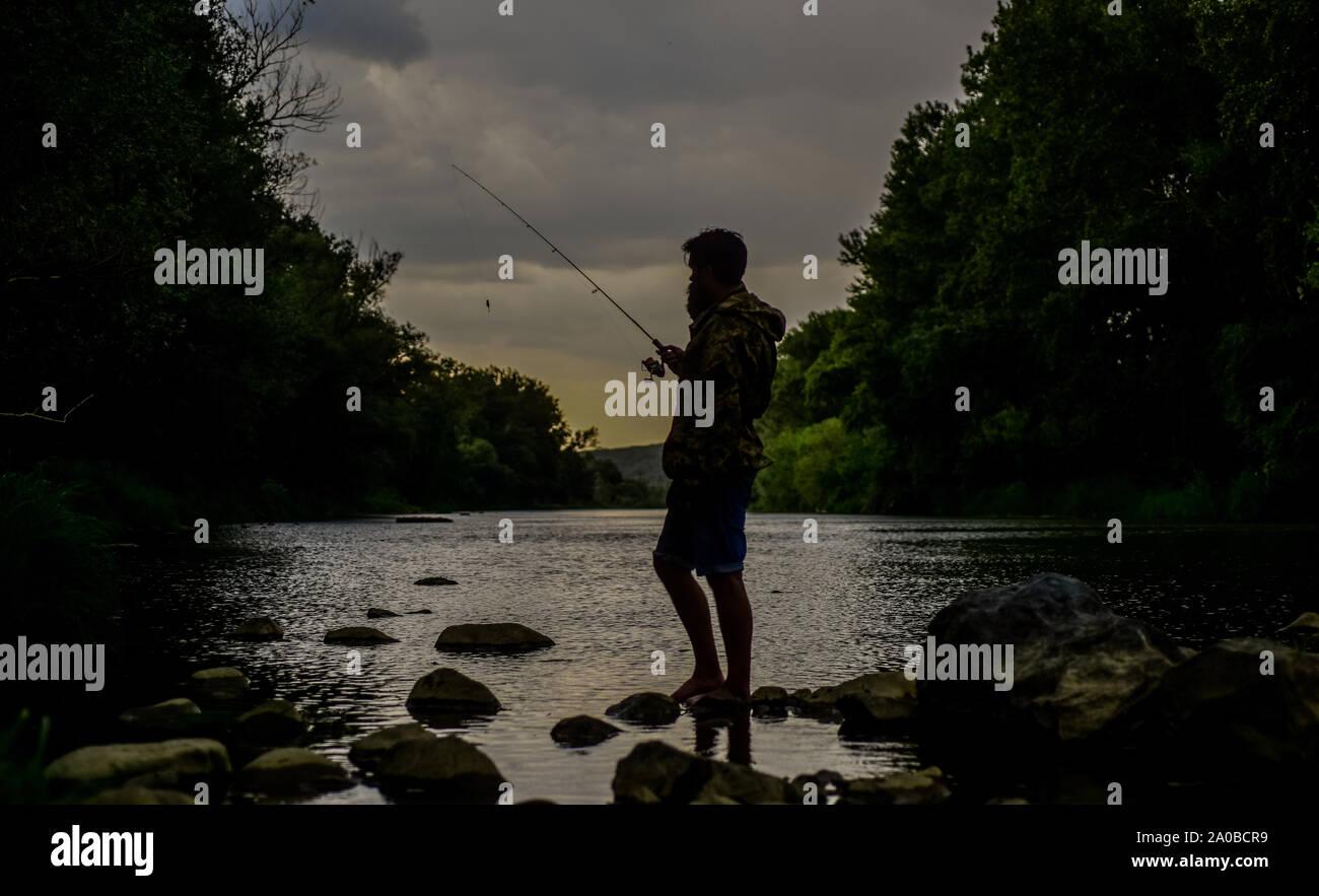 Gute Zeiten. Abend angeln. Sport und Hobby. Sommer Wochenende. Fischer zeigen Angeln Technik verwenden, um Stange. Erfahrene fisher Warten für Fische im Wasser. man Fische fangen. reifer Mann Fliegenfischen. Stockfoto