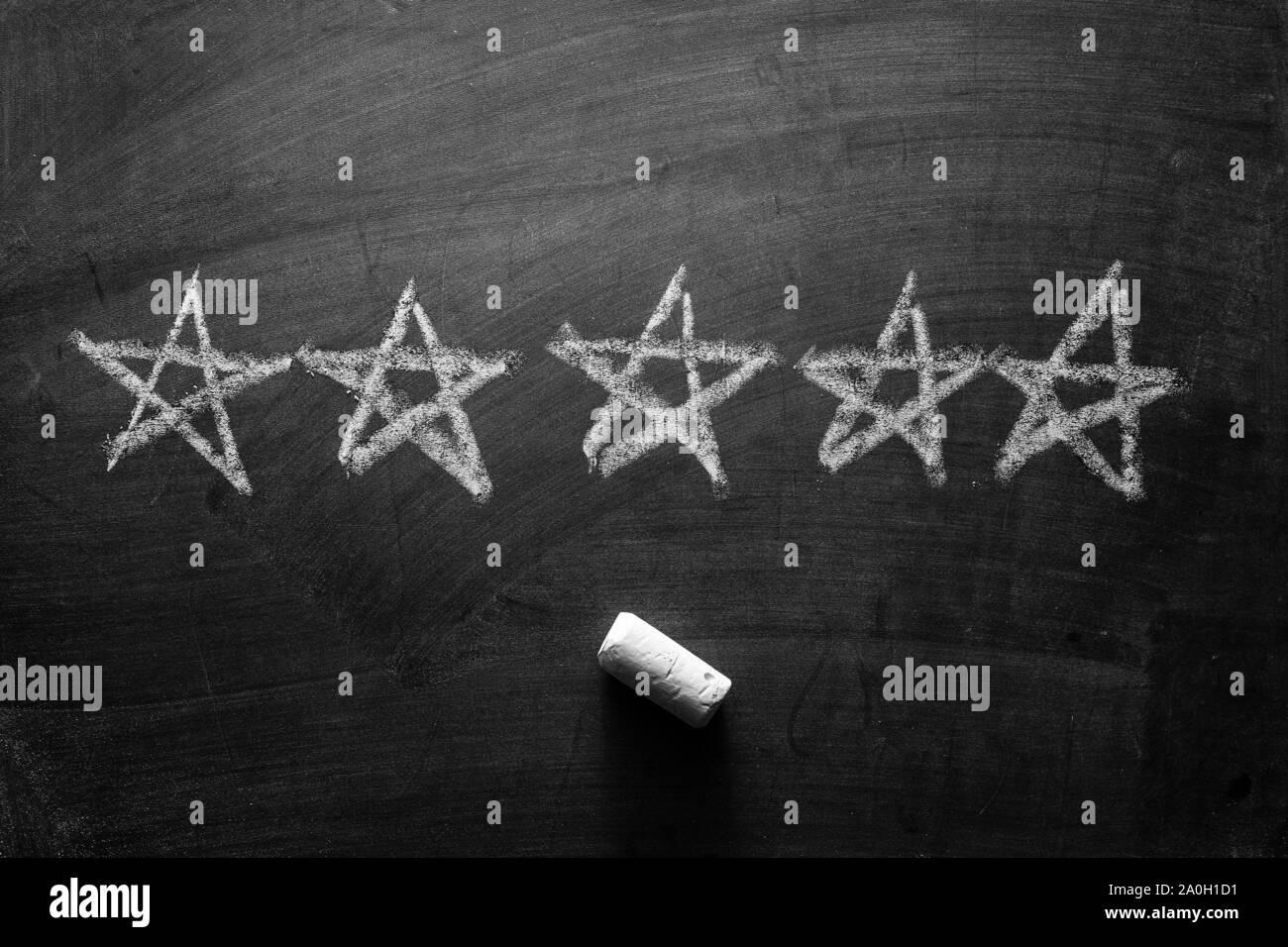 Fünf Hand skizziert weiße Sterne auf einer Schiefertafel oder Tafel mit Stück Kreide unten in einem Konzept der Einstufung für hervorragende Leistung Stockfoto