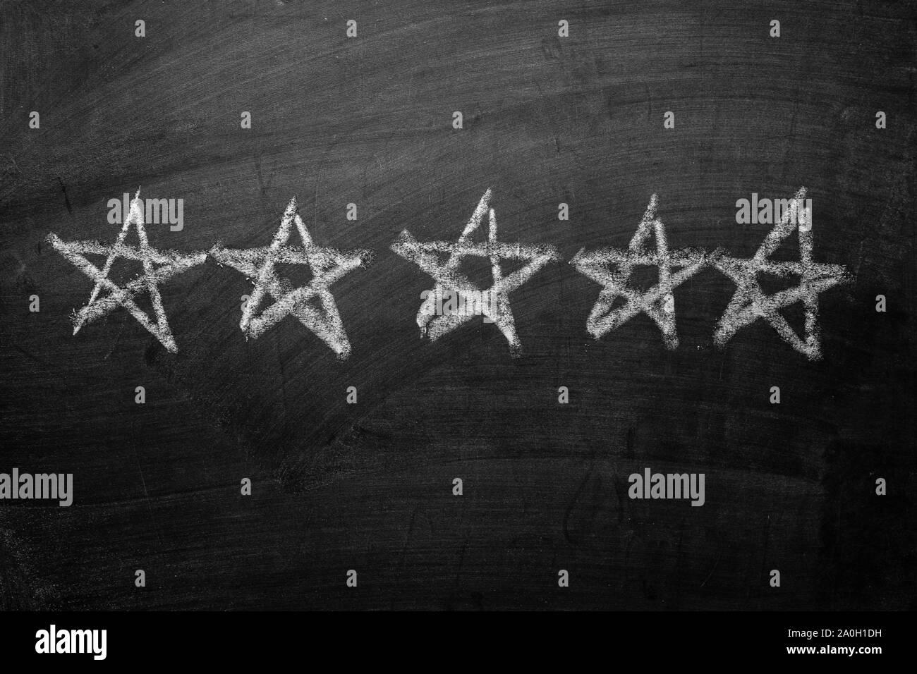 Fünf Sterne hand weißer Kreide auf einer Tafel in einer Reihe konzeptioneller eines fünf Sterne für Excellence gezeichnet Stockfoto