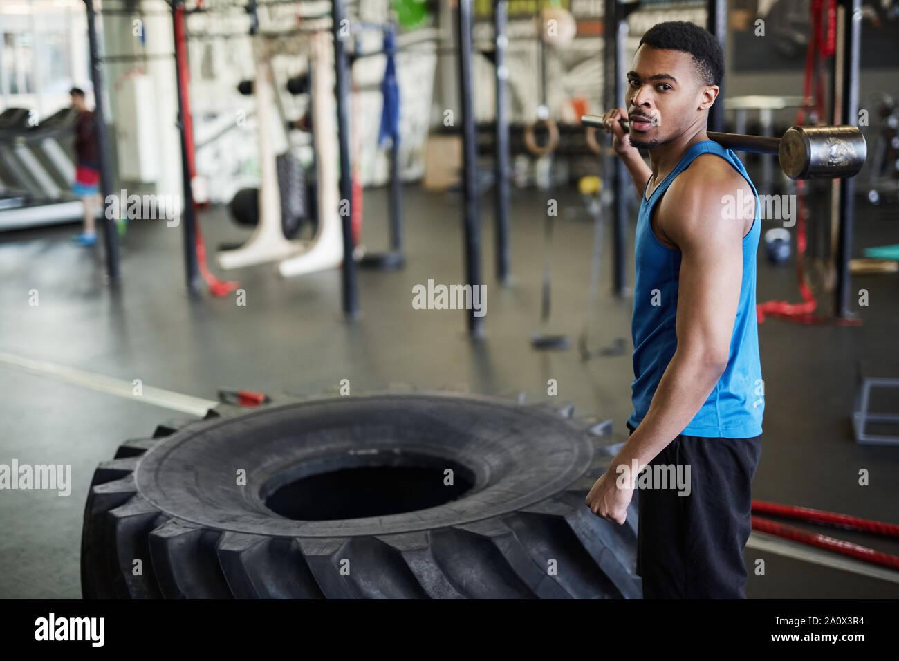 Portrait von Stattlichen muskulösen Mann an der Kamera stehend, durch schweren Reifen während Cross Training im modernen Fitnessraum, Kopie Raum Stockfoto
