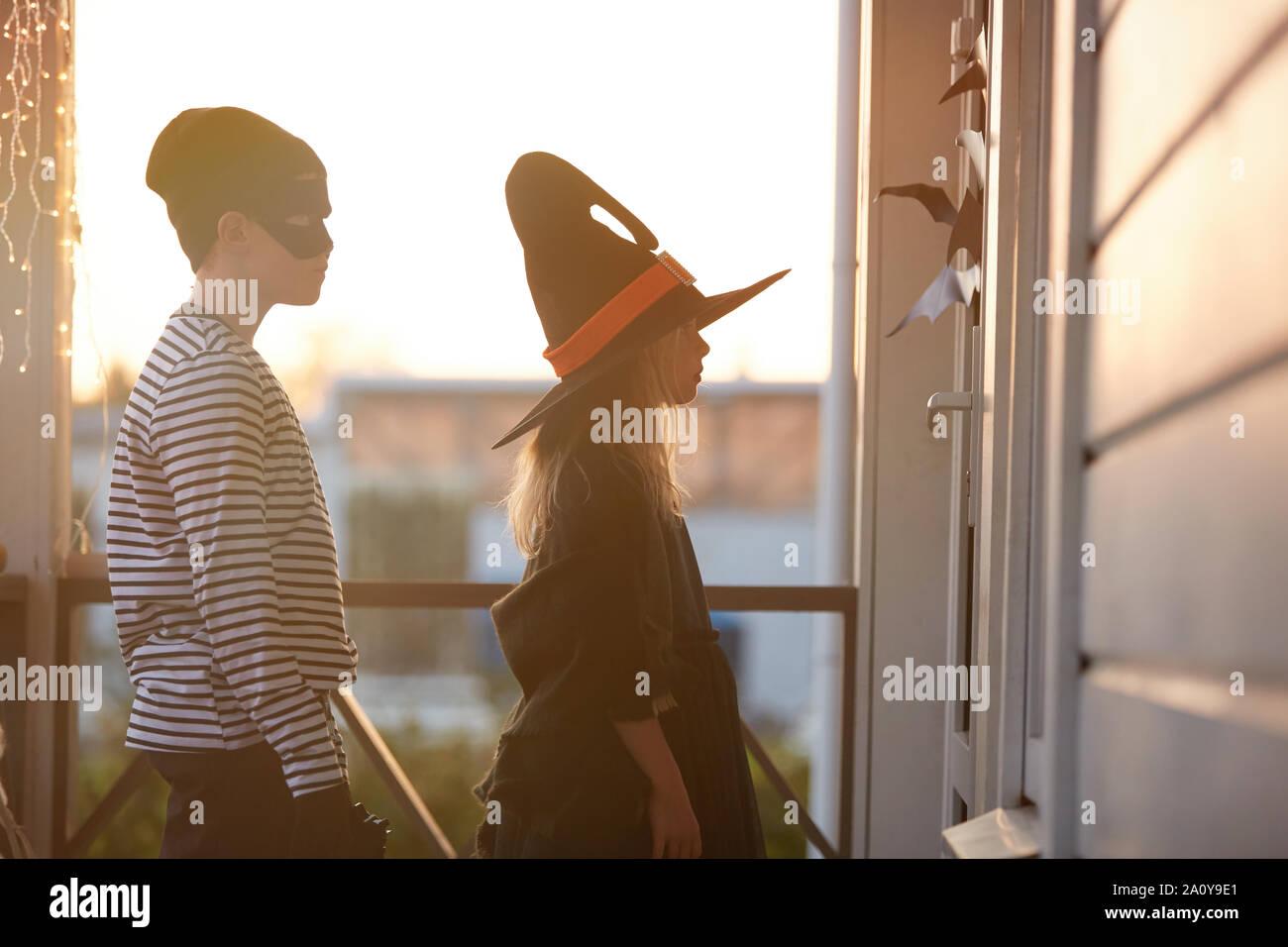 Seitenansicht Porträt zweier Kinder warten durch die Tür, während Süßes oder Saures auf Halloween, kopieren Raum Stockfoto