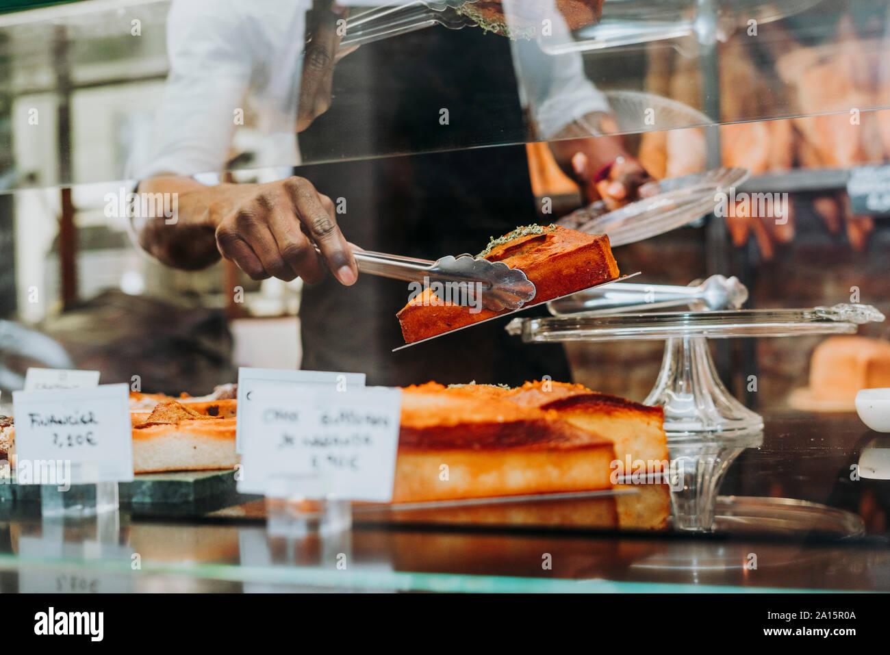 Mann bei der Arbeit in einer Bäckerei, ein Stück Kuchen auf den Teller Stockfoto