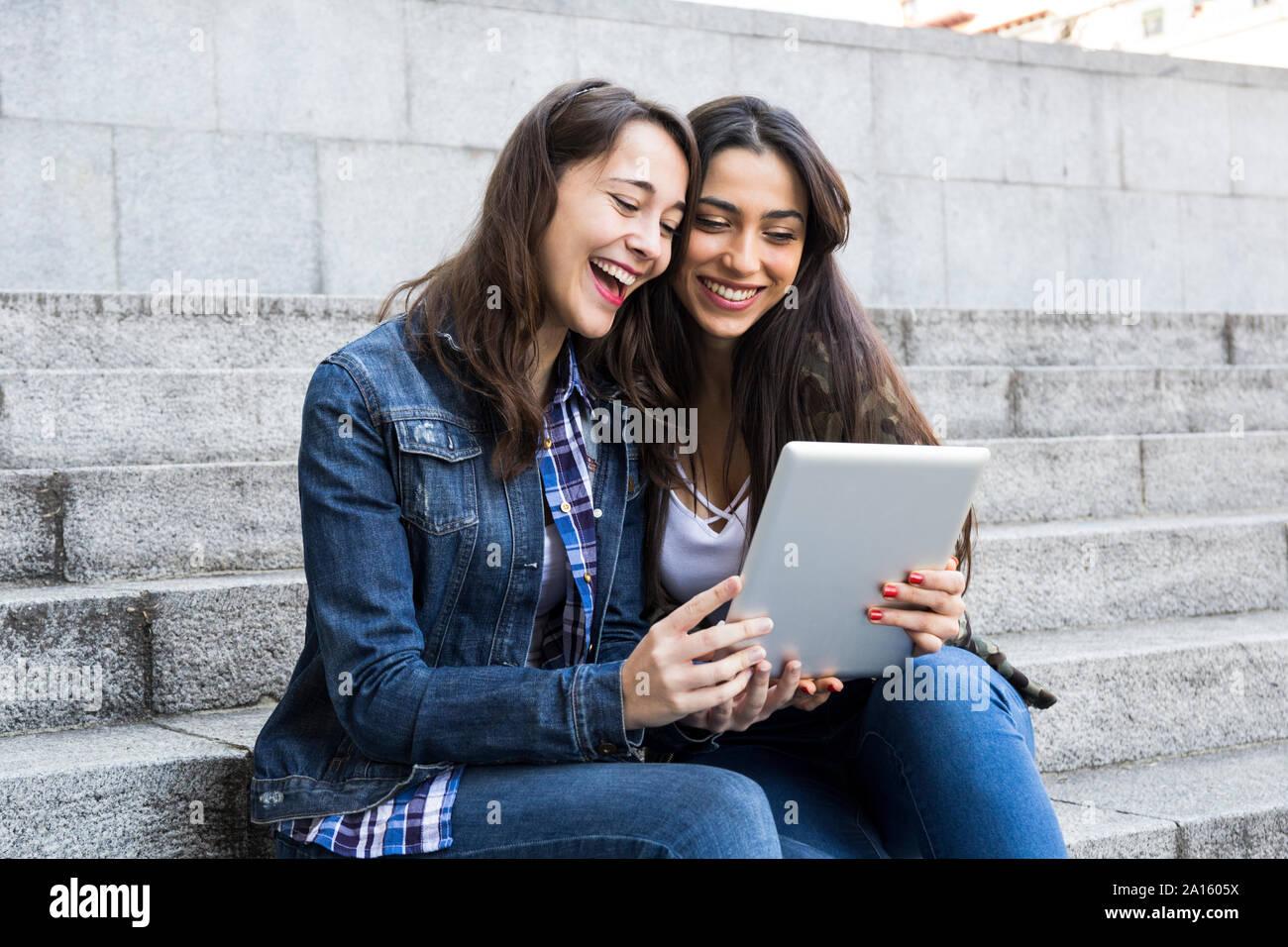 Glückliche junge Frauen beobachten Tablette auf Schritte gemeinsam in Madrid, Spanien Stockfoto