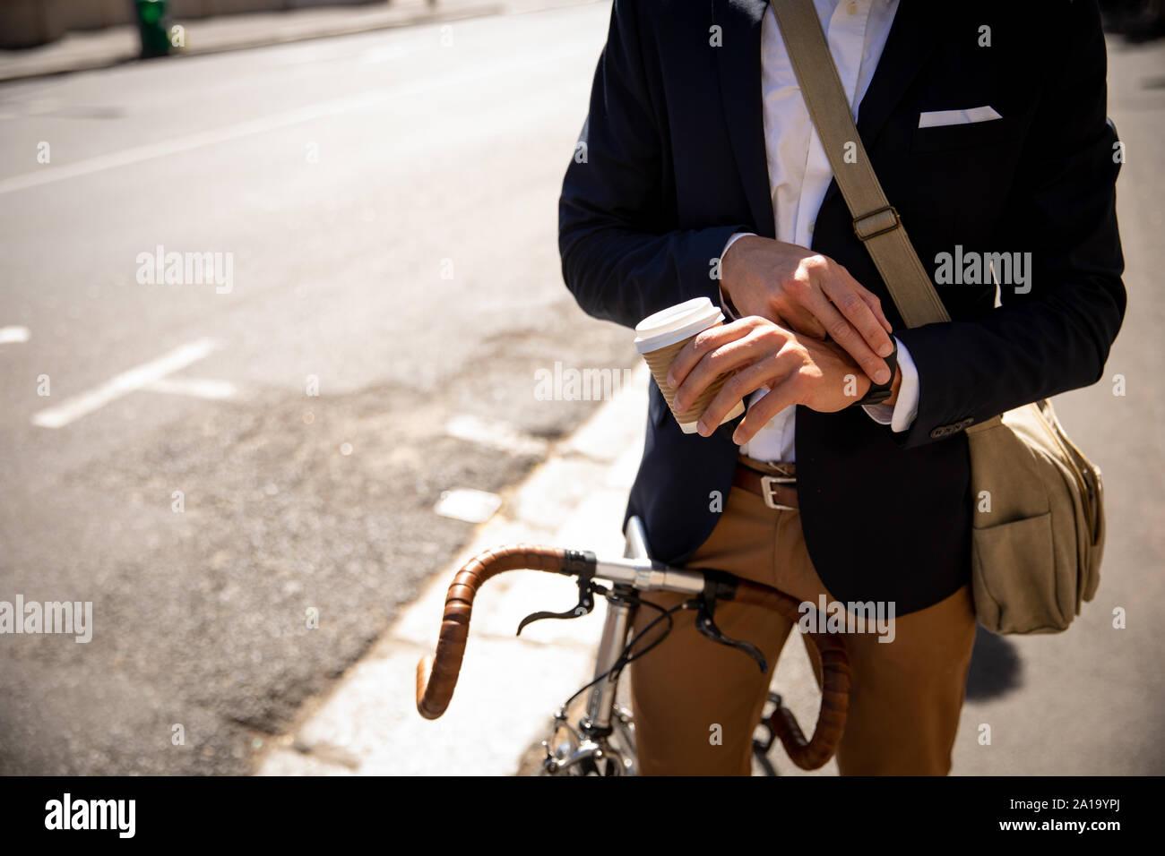 Junge professionelle man Kontrolle Zeit und sitzt auf einem Fahrrad Stockfoto