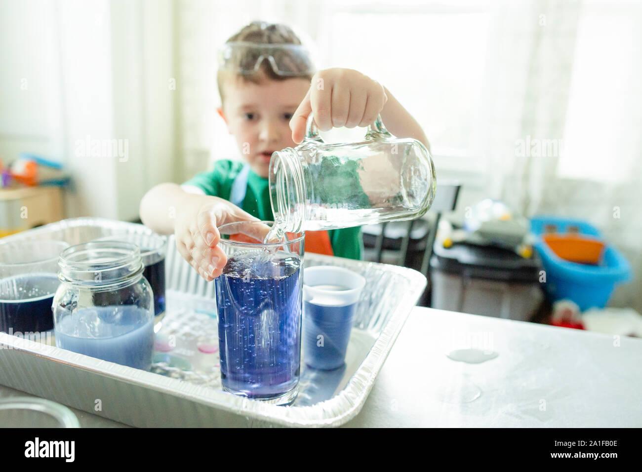 Elementare alter Junge gießt Wasser in ein Glas während Du einen Stamm Projekt Stockfoto