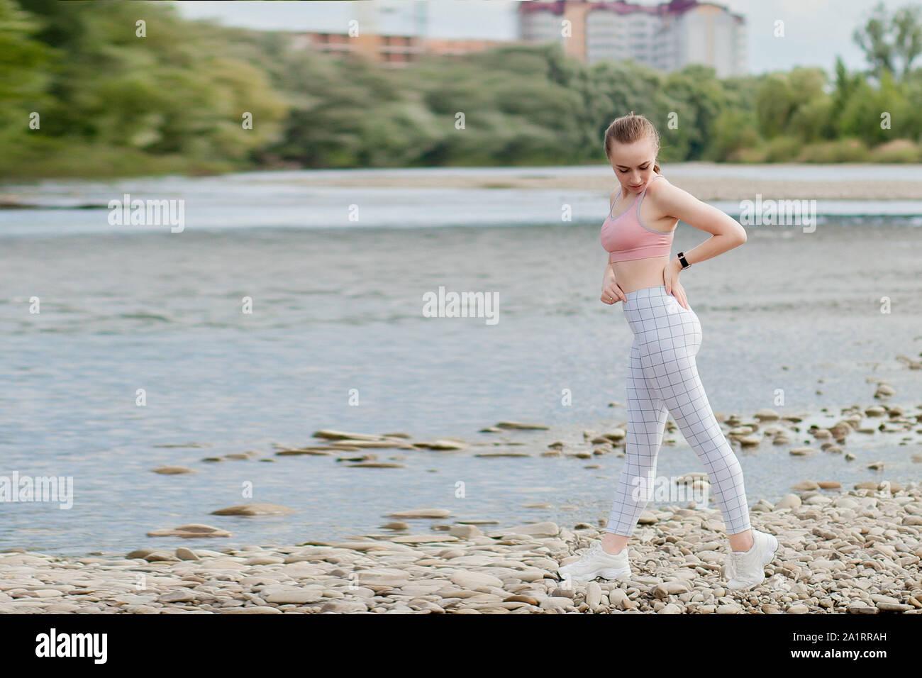 Mädchen im Sport Uniformen macht eine Strecke auf dem Fluss Stockfoto