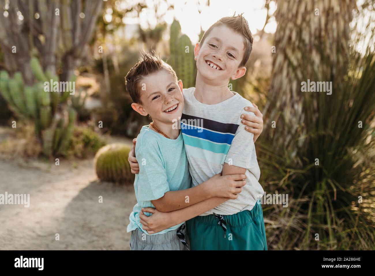 Fröhliche Brüder umarmen und lächelnd im sonnigen Kaktus Garten Stockfoto