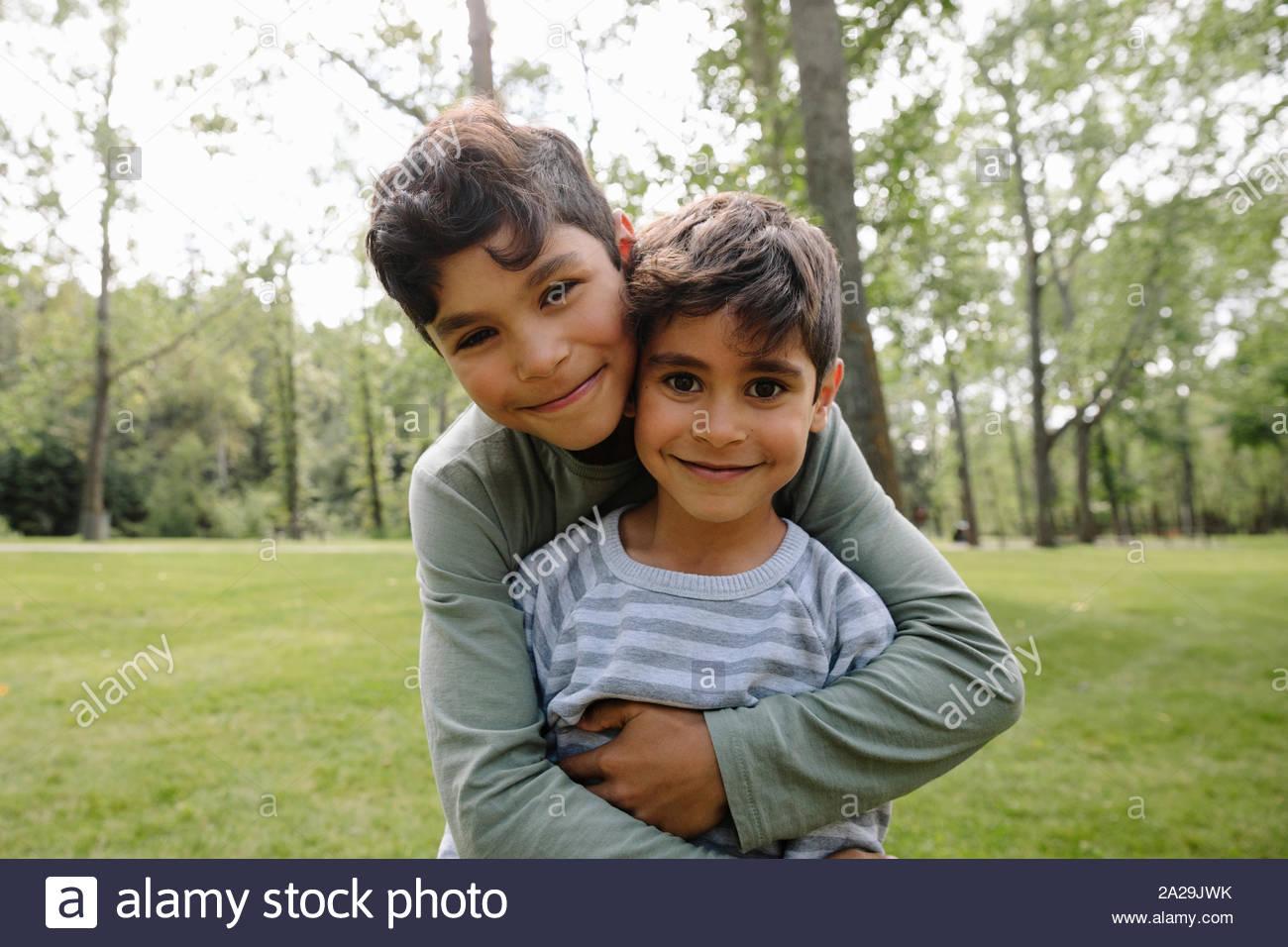 Porträt von zwei Brüder umarmen in städtischen Park Stockfoto