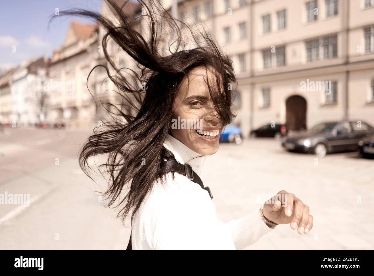 Sorglos Frau mit Haare im Wind in der Stadt. München, Deutschland Stockfoto