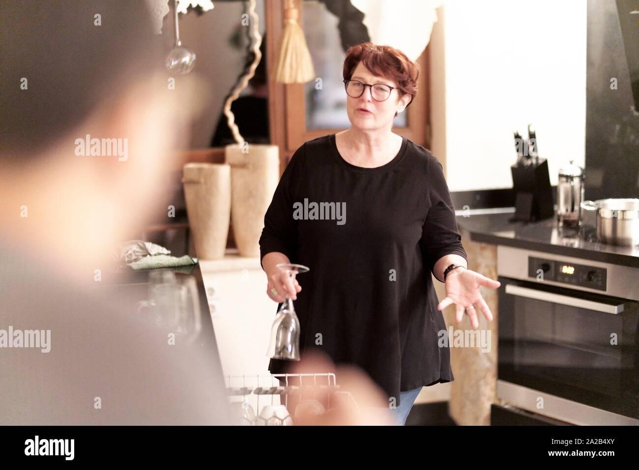 Frau im Gespräch mit Gegenstück in der Küche, während die Sortierung Geschirr in der Spülmaschine Stockfoto