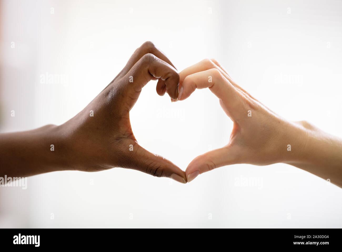Nahaufnahme von Multirassischen's Freundin Hände sichtbar Herzform vor weißem Hintergrund Stockfoto