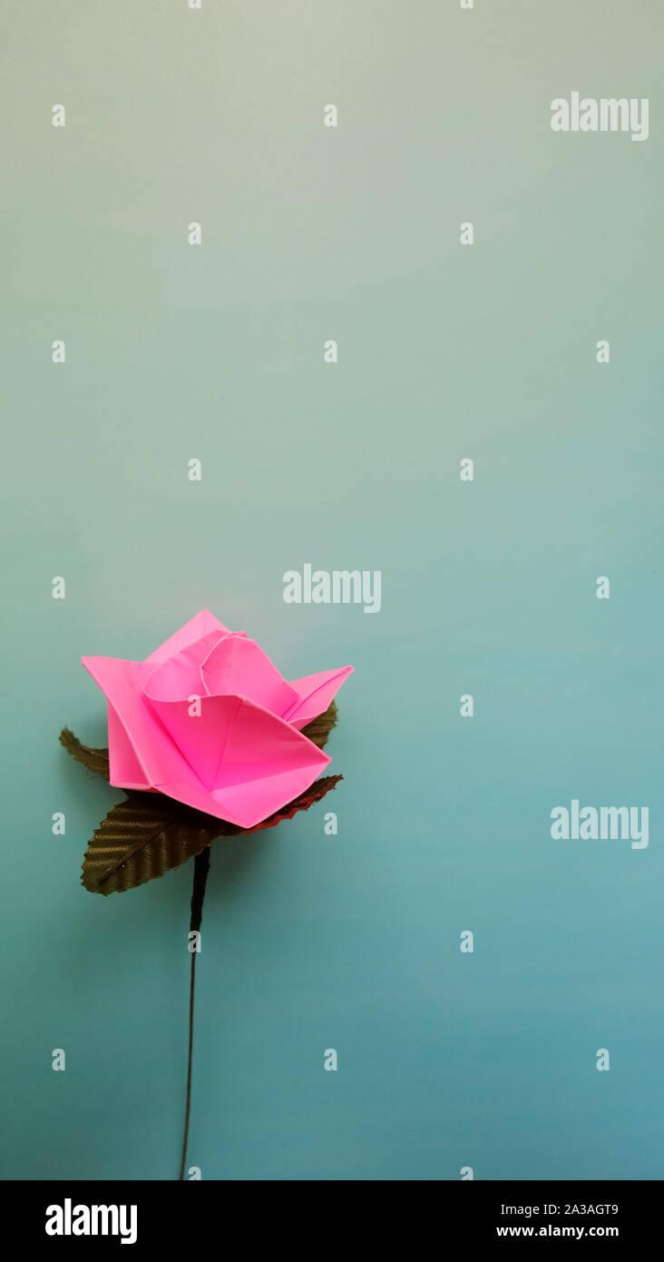 Ein rosa Papier Rose, auf einem blauen Hintergrund mit Farbverlauf. Stockfoto
