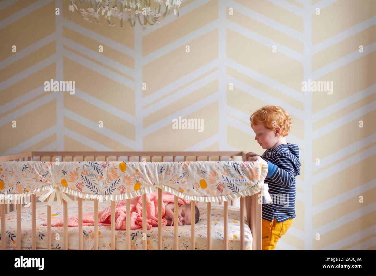 Toddler boy peeking in über Krippe Schiene bei neugeborenen Babys schlafen in der Krippe Stockfoto