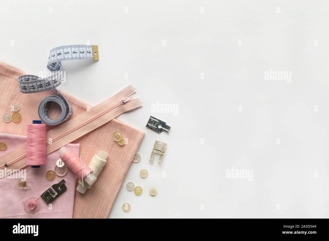 Nähzubehör und Stoff auf einem weißen Hintergrund. Nadeln, Knöpfe, Stoff, Nähgarne und nähen Zentimeter. top Aussicht, flatlay Stockfoto
