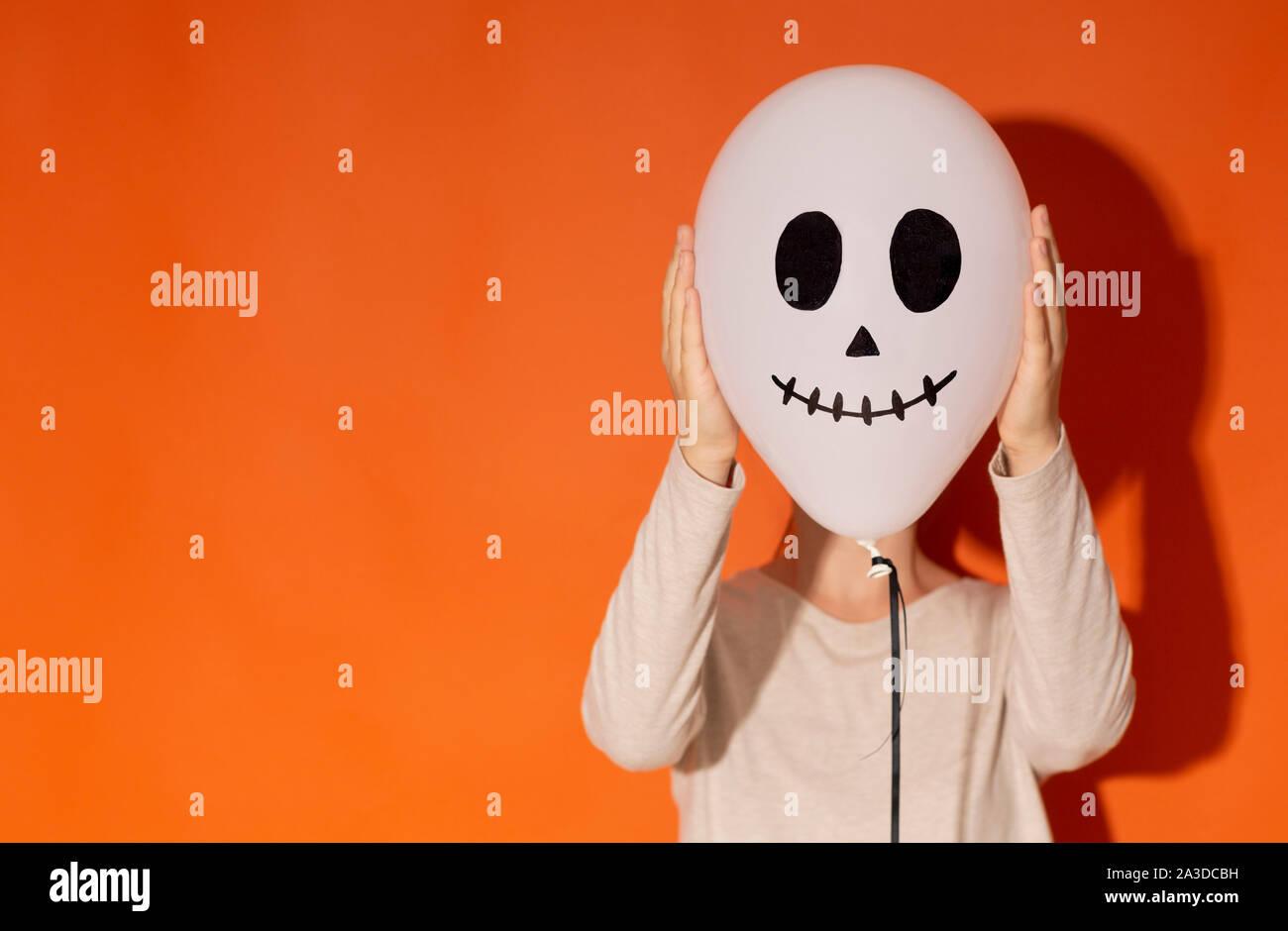 Frau verbergen ihr Gesicht neben Ballon mit Gesicht auf Orange Stockfoto