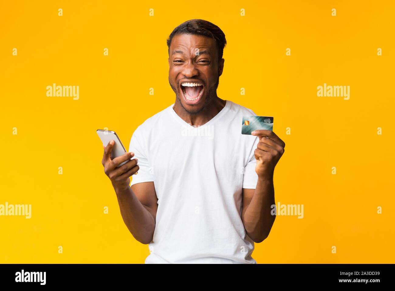 Afro Kerl Holding Telefon und Kreditkarte Schreien, Gelber Hintergrund Stockfoto