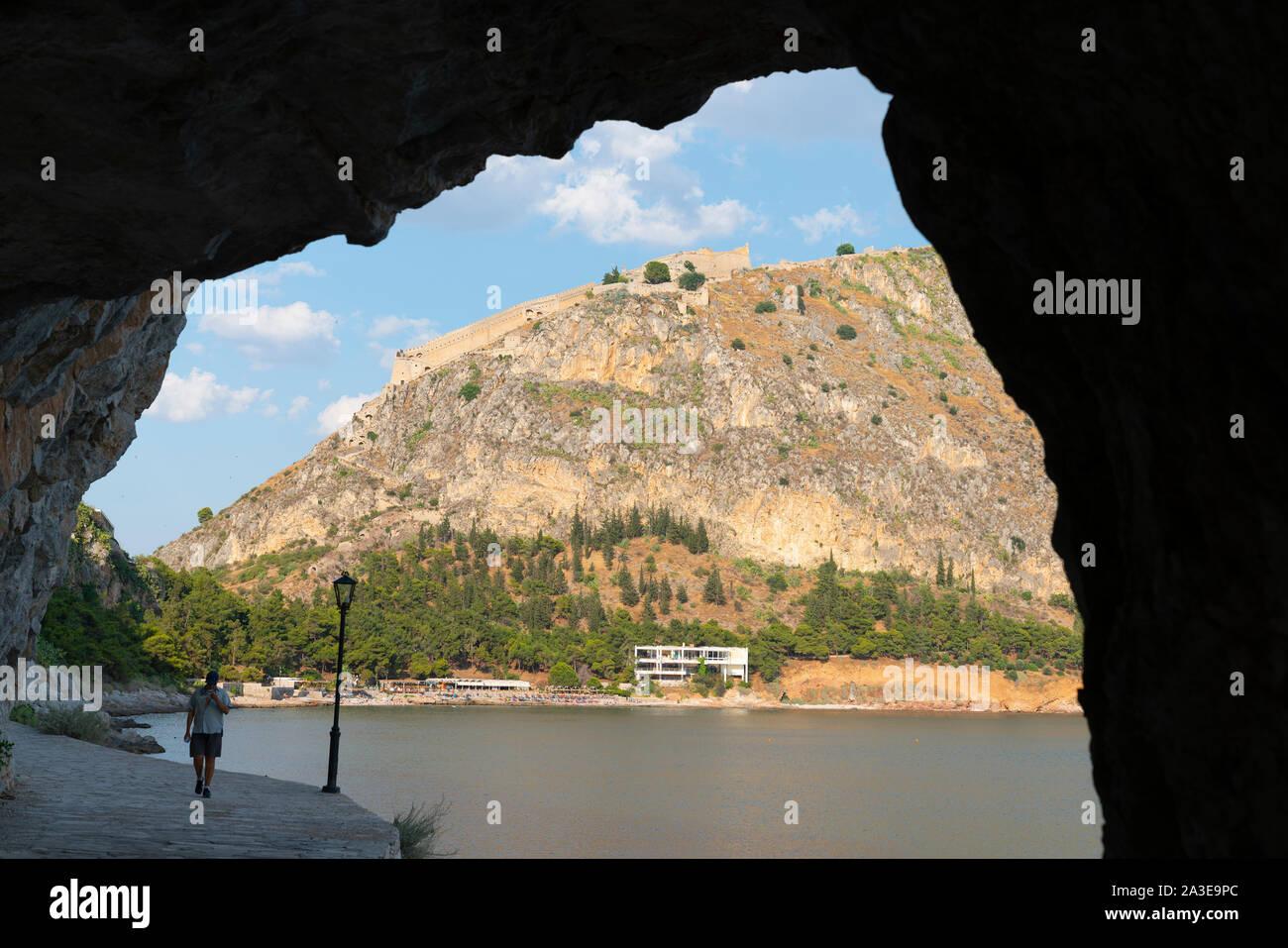 Nafplio Griechenland - 19 Juli 2019; Rock arch im Silhouette mit Blick über den Strand von Arvanitia und Resort mit Palimidi Fort auf dem Hügel. Stockfoto