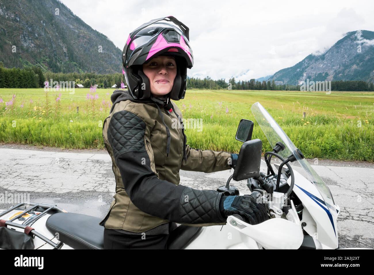 Eine Frau reitet ihr Motorrad an einem bewölkten Sommertag. Stockfoto