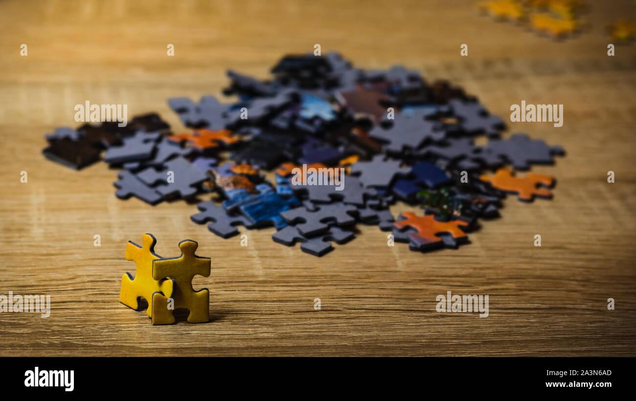 Zwei gelbe Rätsel an eine große Gruppe von anderen Rätsel suchen. Konzept der Versuch, einer Gruppe beizutreten. Stockfoto