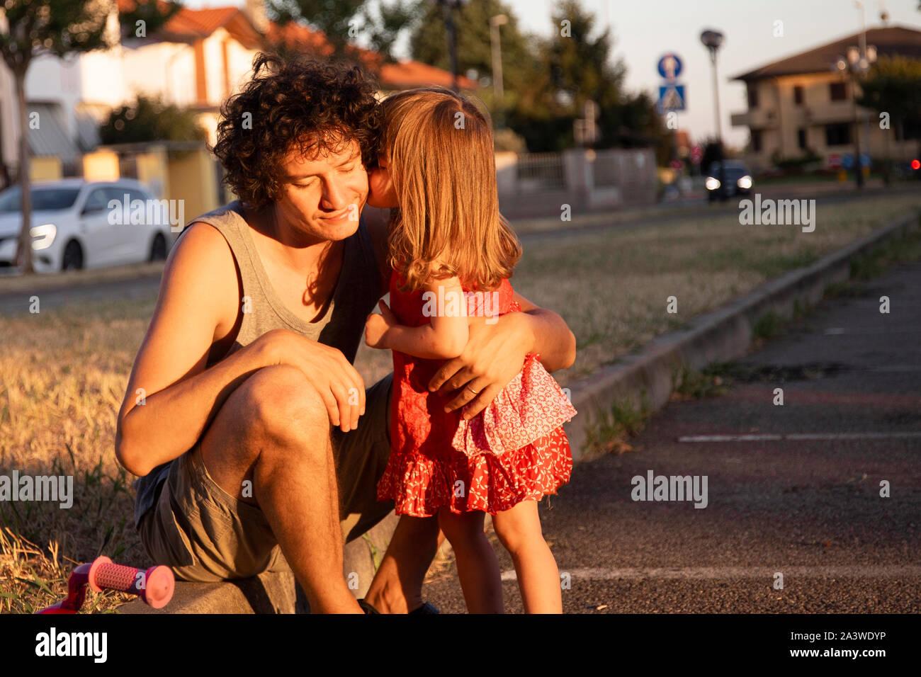 Kleines Kind Tochter auf einem Fahrrad küsste ihre jungen Vater bei Sonnenuntergang im Freien. Kopieren Sie Platz auf der rechten Seite. Stockfoto