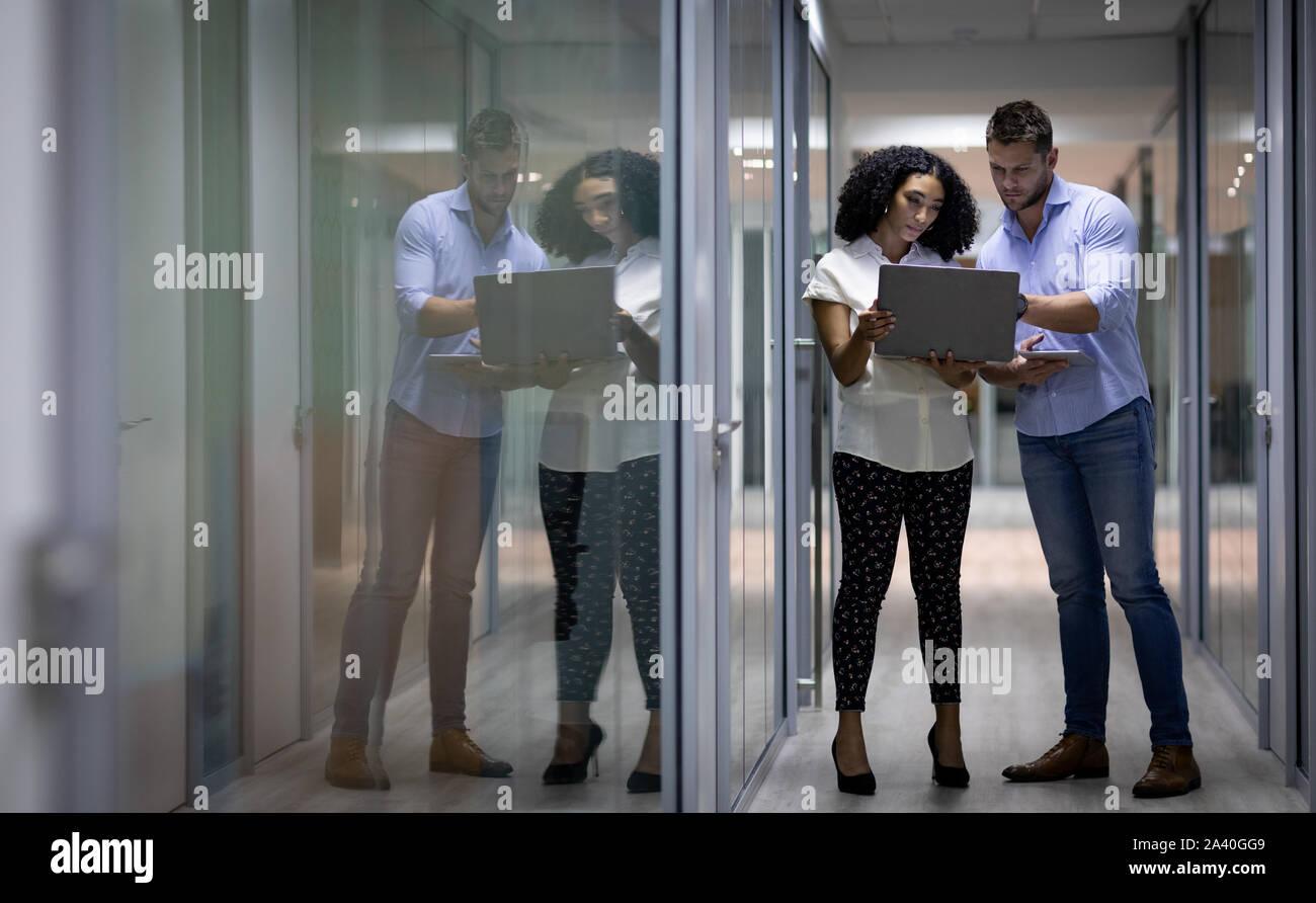 Zwei junge kreative Fachleute, die spät in einem modernen Büro Stockfoto