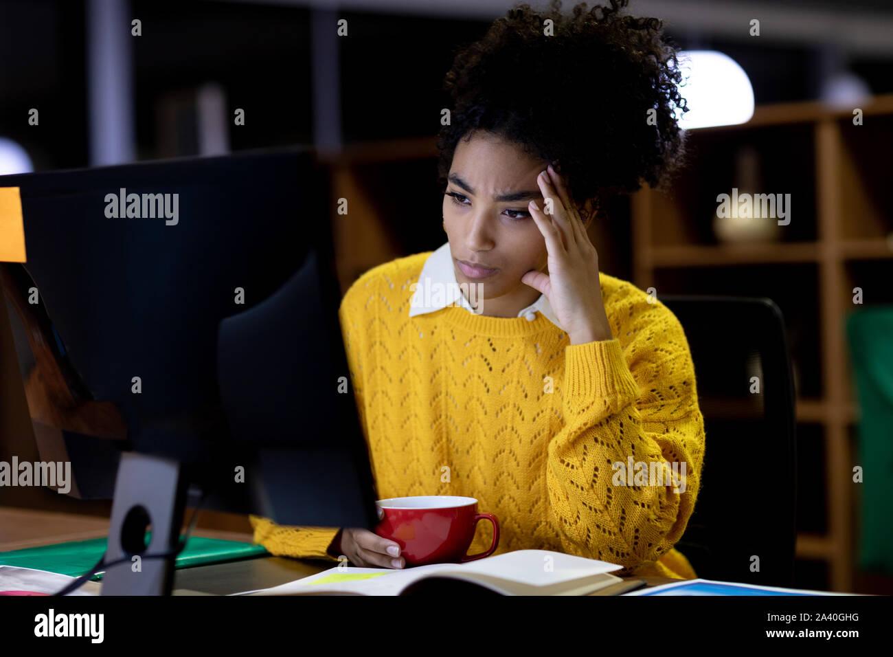 Junge weibliche professionelle arbeiten spät in kreative Büro Stockfoto
