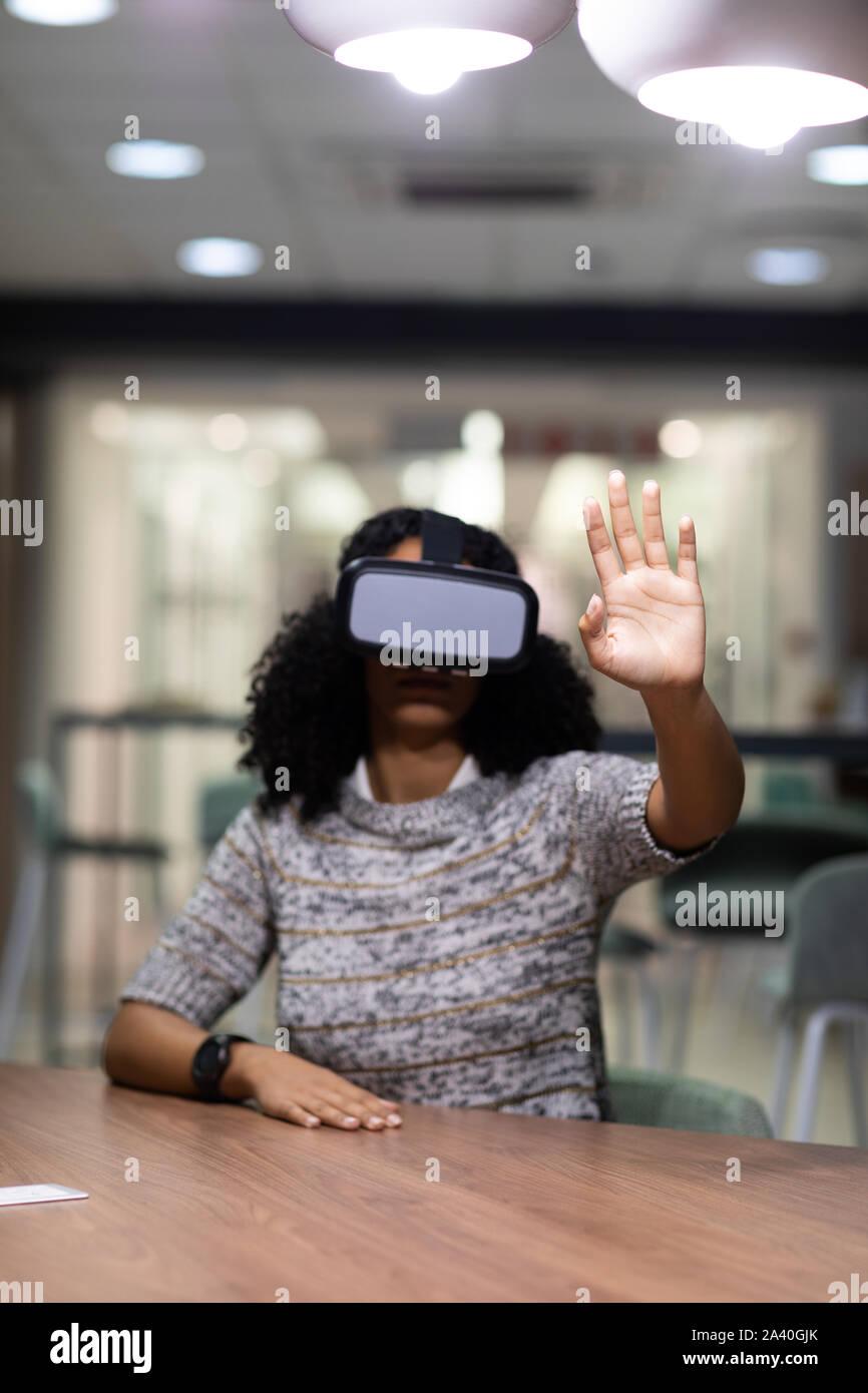 Junge weibliche professionelle arbeiten spät in Creative Office mit VR Stockfoto