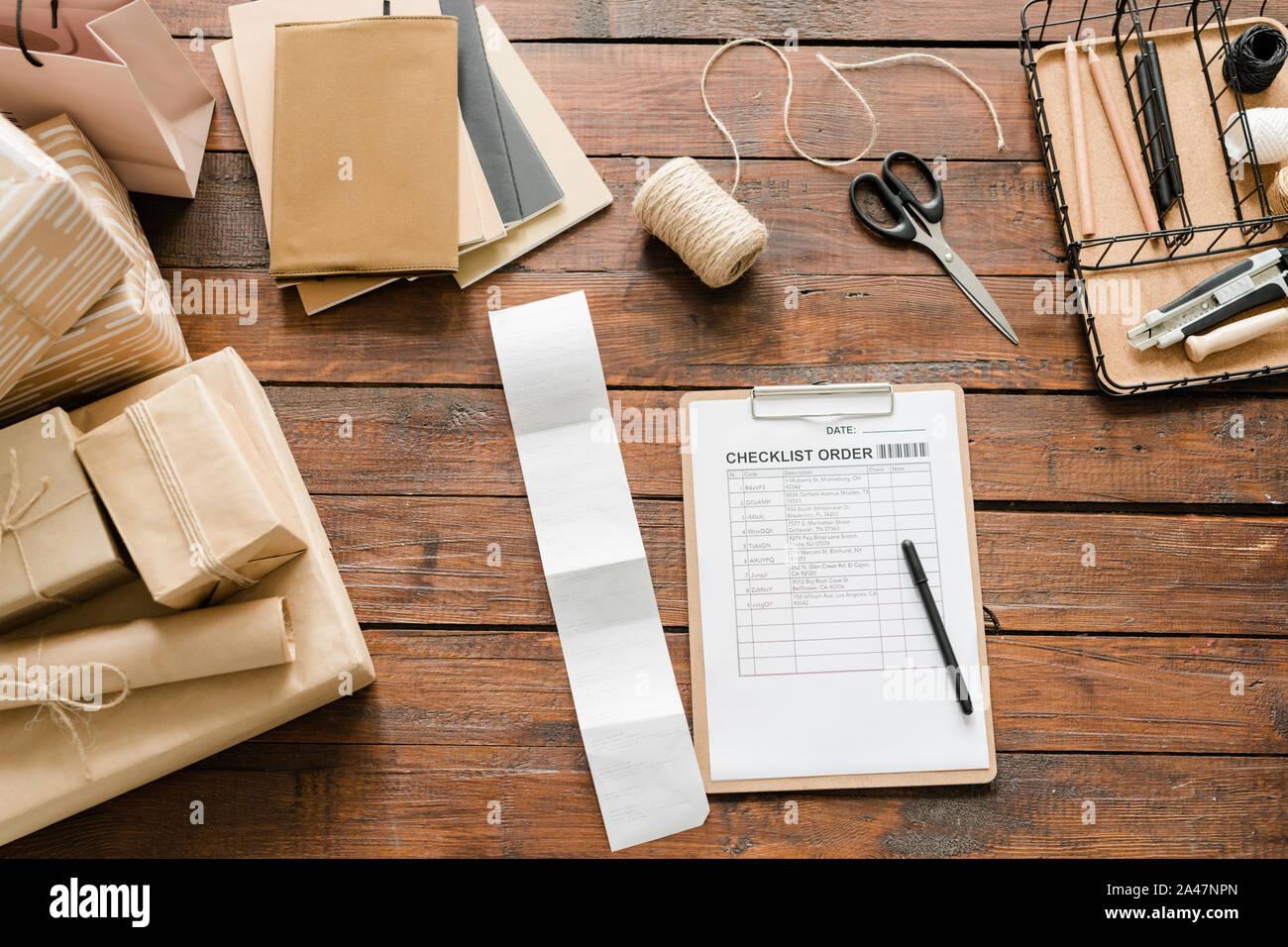 Blick von oben auf die Checkliste um die verpackten Geschenke und verpacken Produkte umgeben Stockfoto