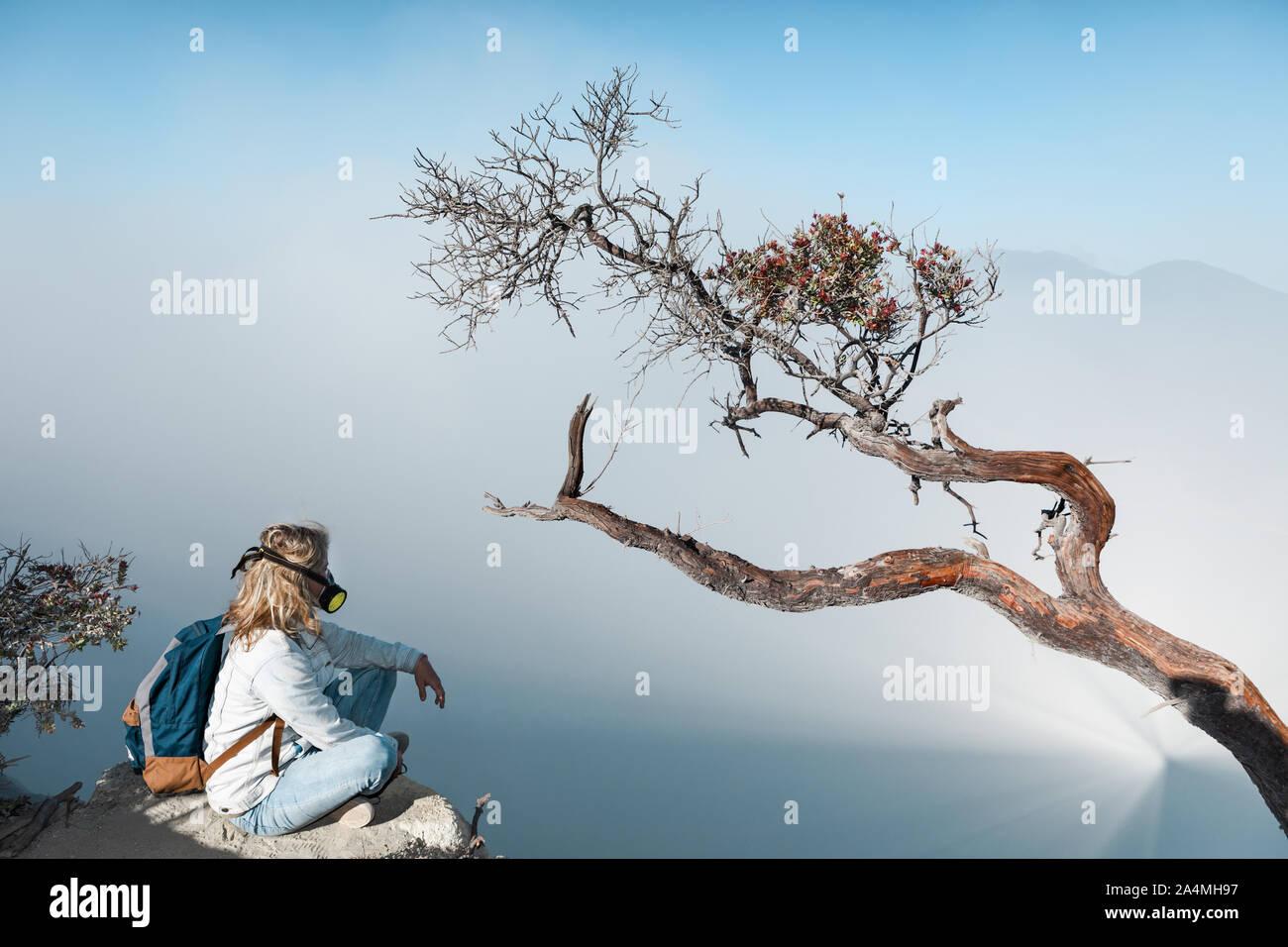 Junge Frau in Schutzmaske auf dem Gipfel des aktiven Vulkan Kawah Ijen Krater oben Säure See mit giftigen Dämpfe. Beliebtes Reiseziel. Stockfoto