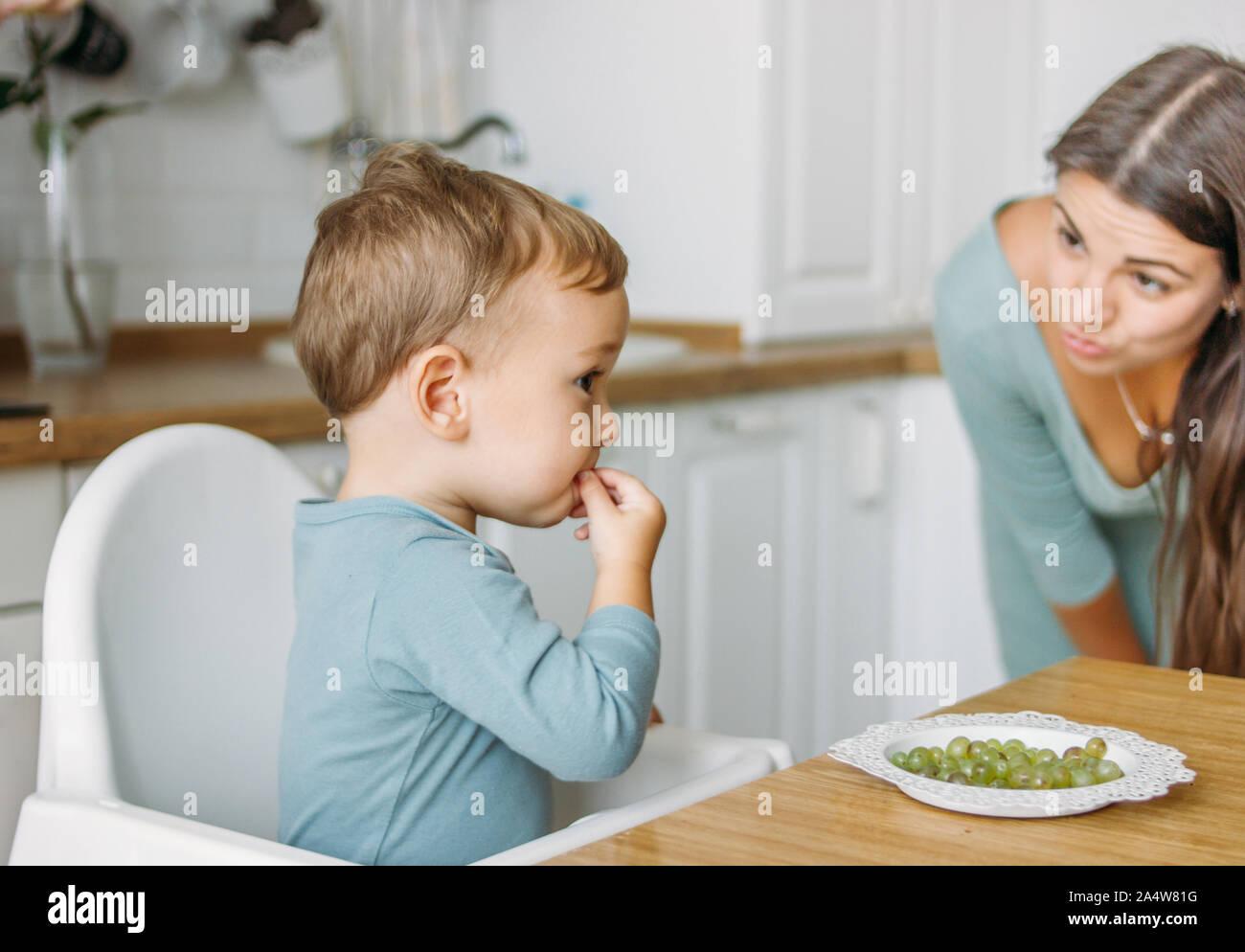 Charmante konzentriert baby boy Essen zunächst Essen Grüne Traube auf die helle Küche zu Hause Stockfoto