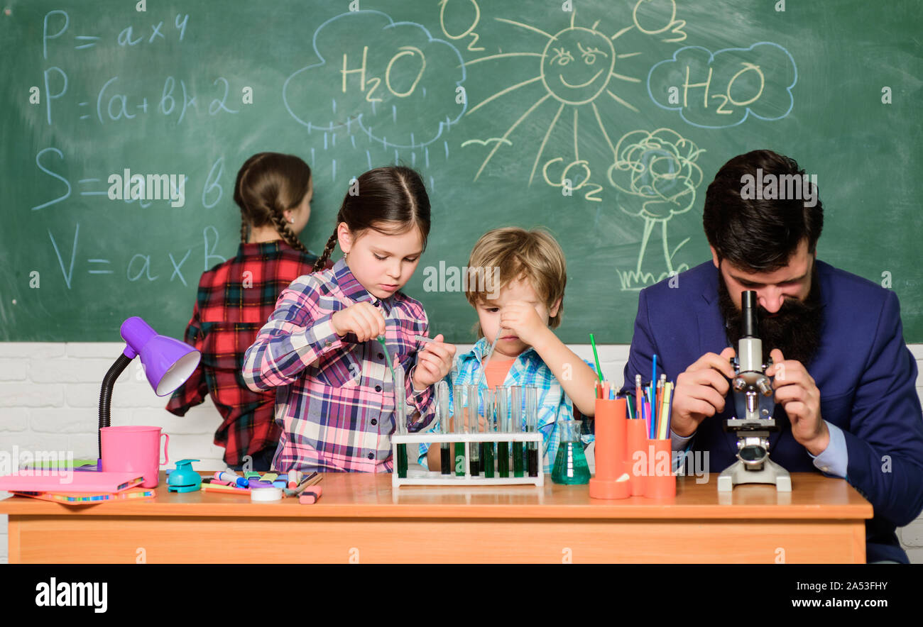 Faszinierende Chemie Lektion. Man bärtige Lehrer und Schüler mit Reagenzgläsern im Klassenzimmer. Beobachten Sie die Reaktion. Wissenschaft ist immer die Lösung. Schule Chemie Experiment. Erklären der Chemie zu Kindern. Stockfoto