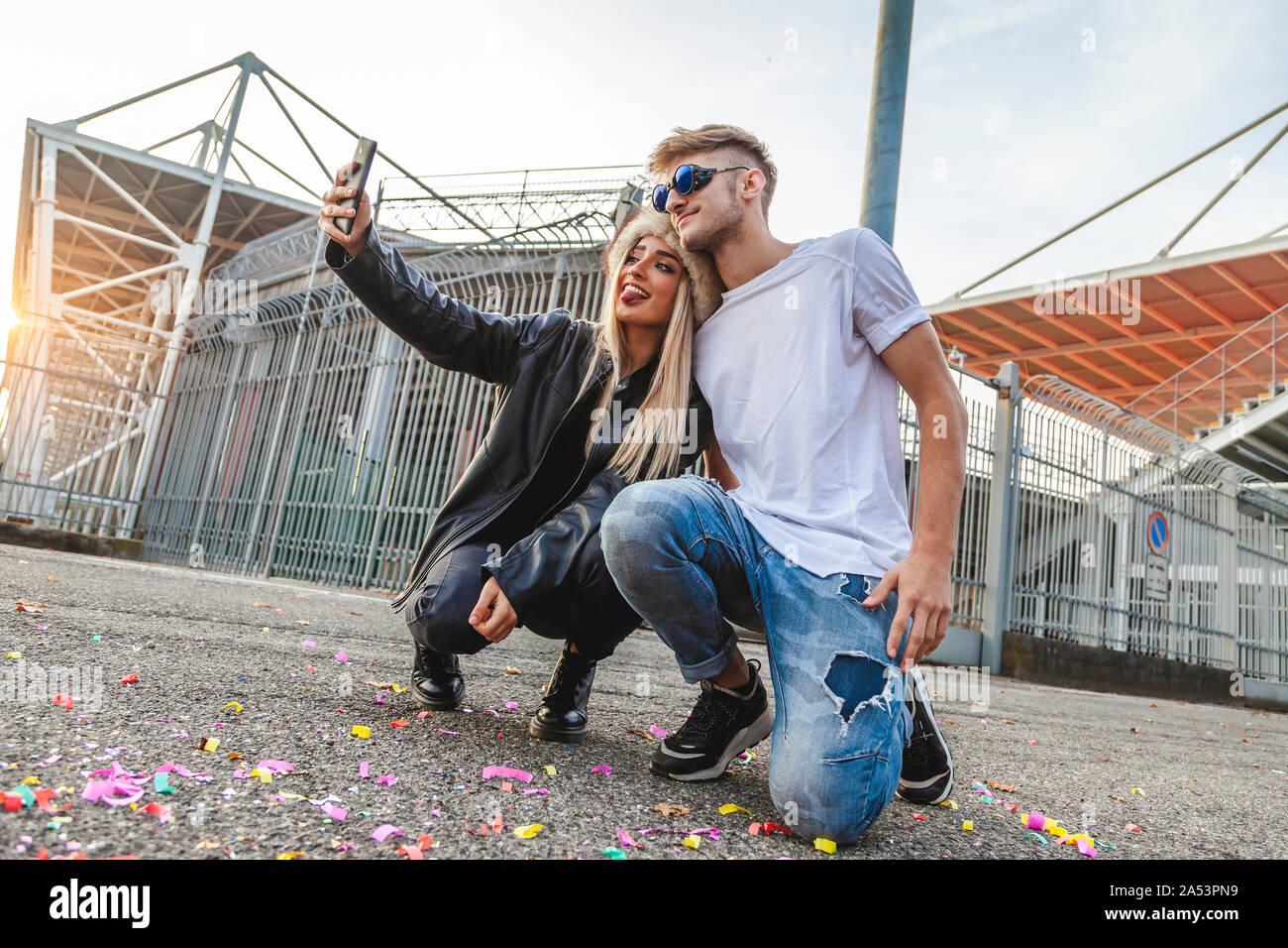 Paar der jungen schönen Liebhaber ein selfie auf dem großen Platz von einem Stadion Stockfoto