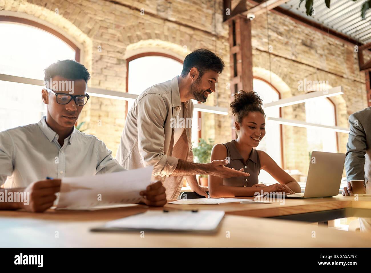 Team bei der Arbeit. Gruppe junger Geschäftsleute zusammen arbeiten und miteinander kommunizieren, während Sie im Büro sitzen Stockfoto