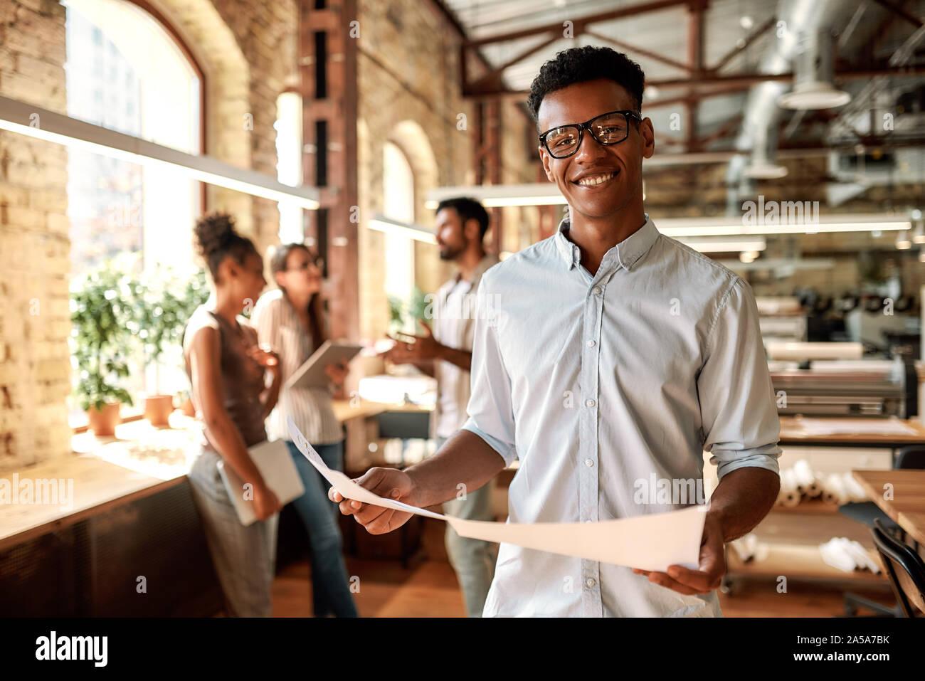 Genießen meine Arbeit. Junge afro-amerikanische Mann, Dokumente und Kamera mit Lächeln, während im modernen Büro stehend Stockfoto