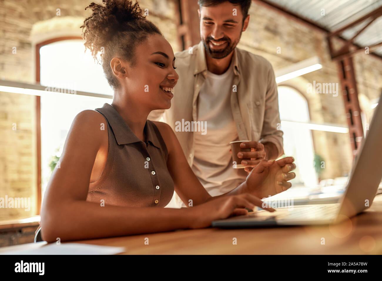 Beratung. Die jungen und freundlichen Mann mit kaffeetasse und im Gespräch mit seinem Kollegen beim zusammen im modernen Büro arbeiten Stockfoto
