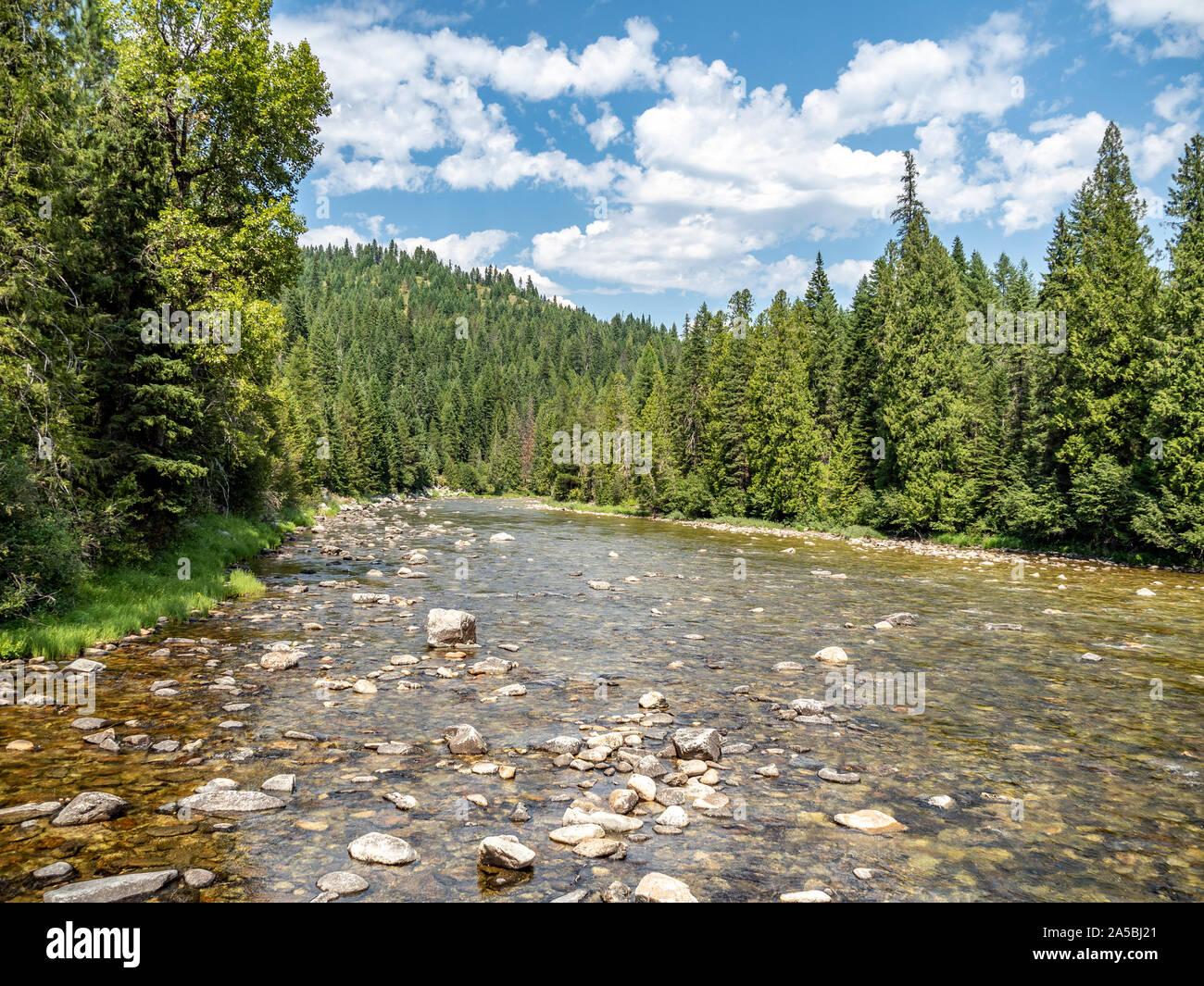 Mountain Stream über felsige Flussbett mit Bäumen und blauen Himmel im Hintergrund fließt. Stockfoto