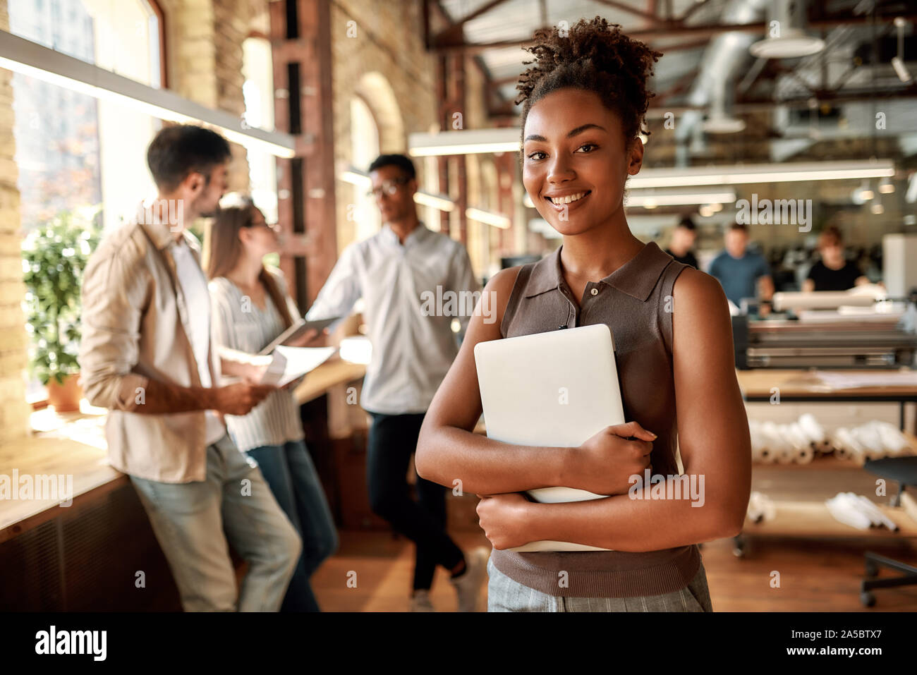 Glücklich, hier zu arbeiten. Junge und fröhliche afro-amerikanische Frau mit Laptop und lächelnd, während im modernen Büro. Stockfoto